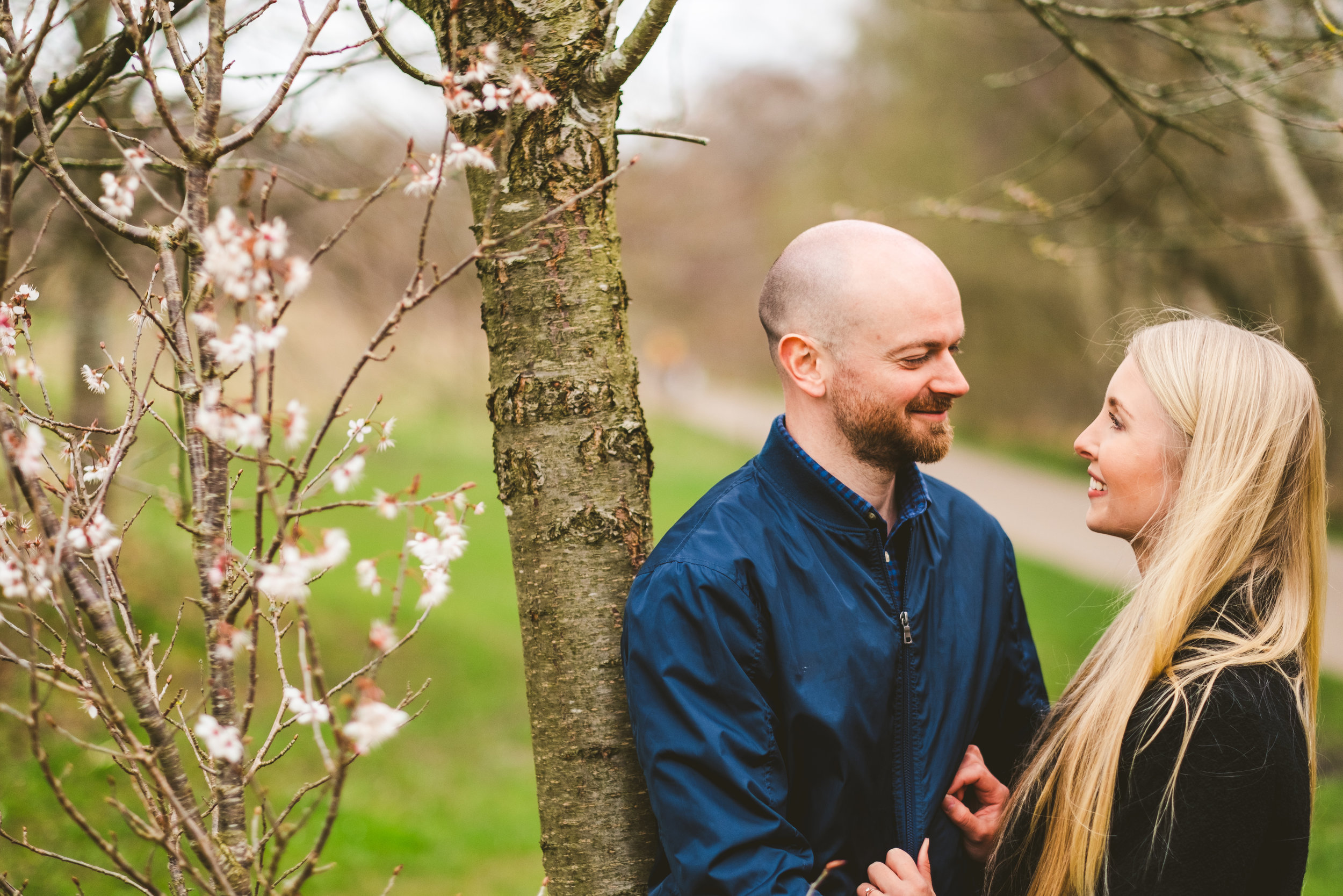 Couple look into each other's eyes while leaning against blossom tree during pre-wedding session in Newcastle