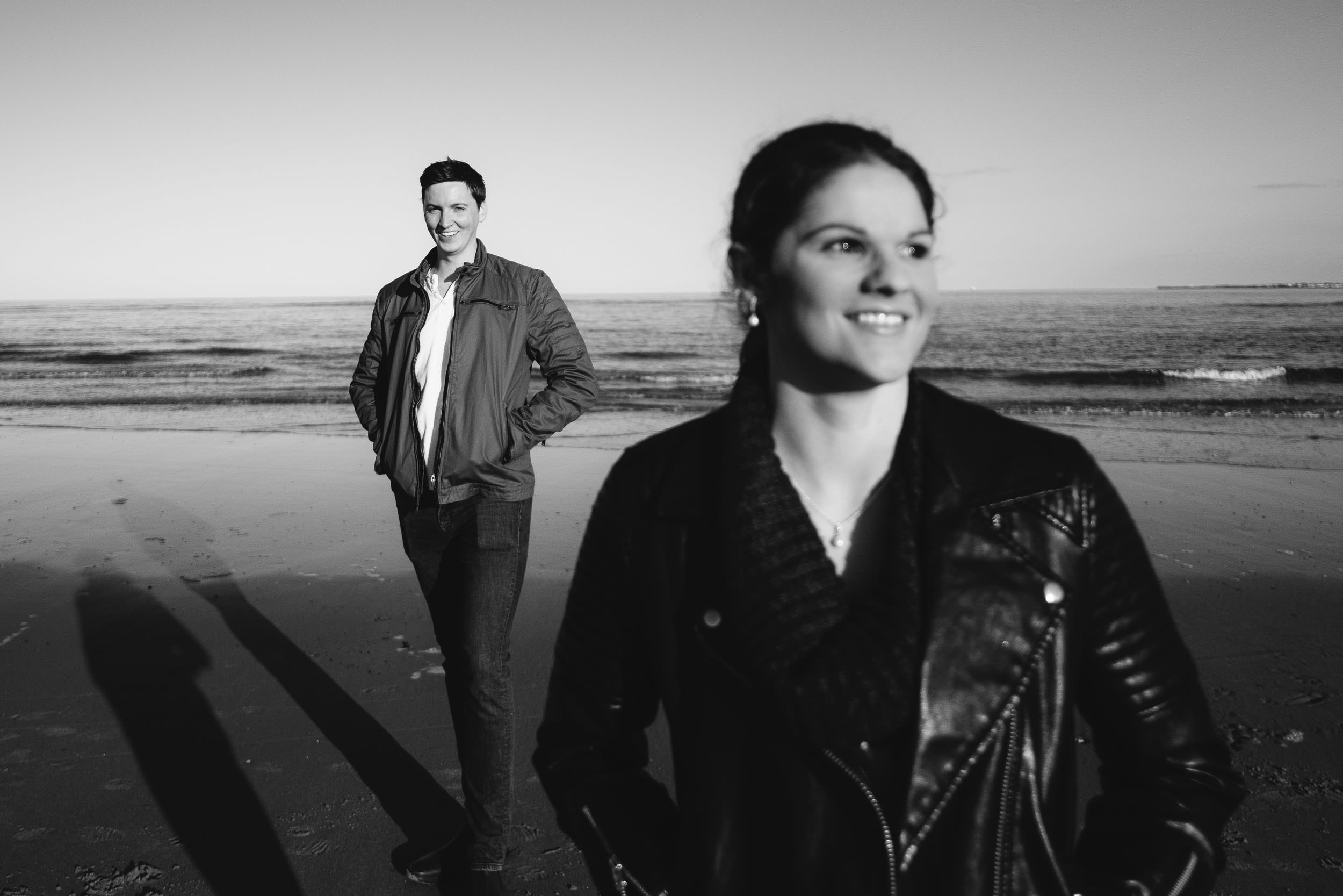 A black and white photo of a couple at the coast with the man in focus and the woman out of focus