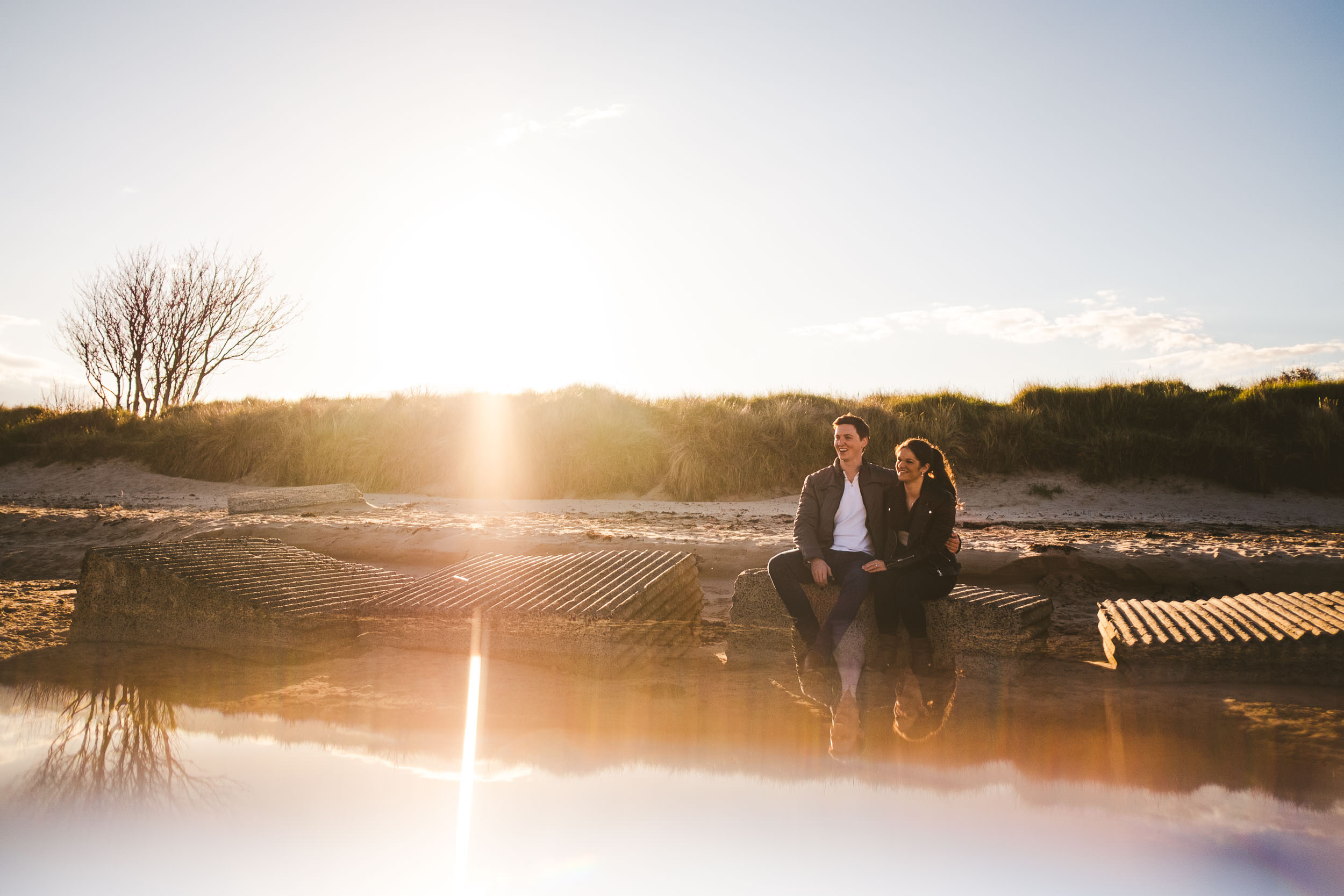 Engaged couple sit on rocks at beach at sunset