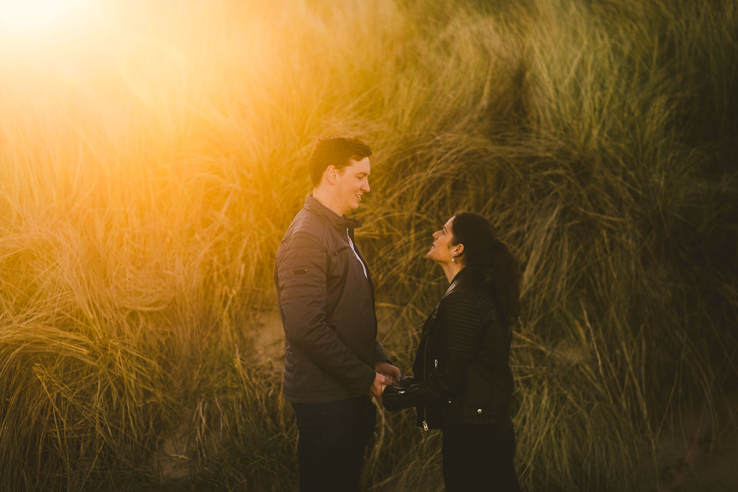 Couple hold hands in front of sand dunes with insane sun flare