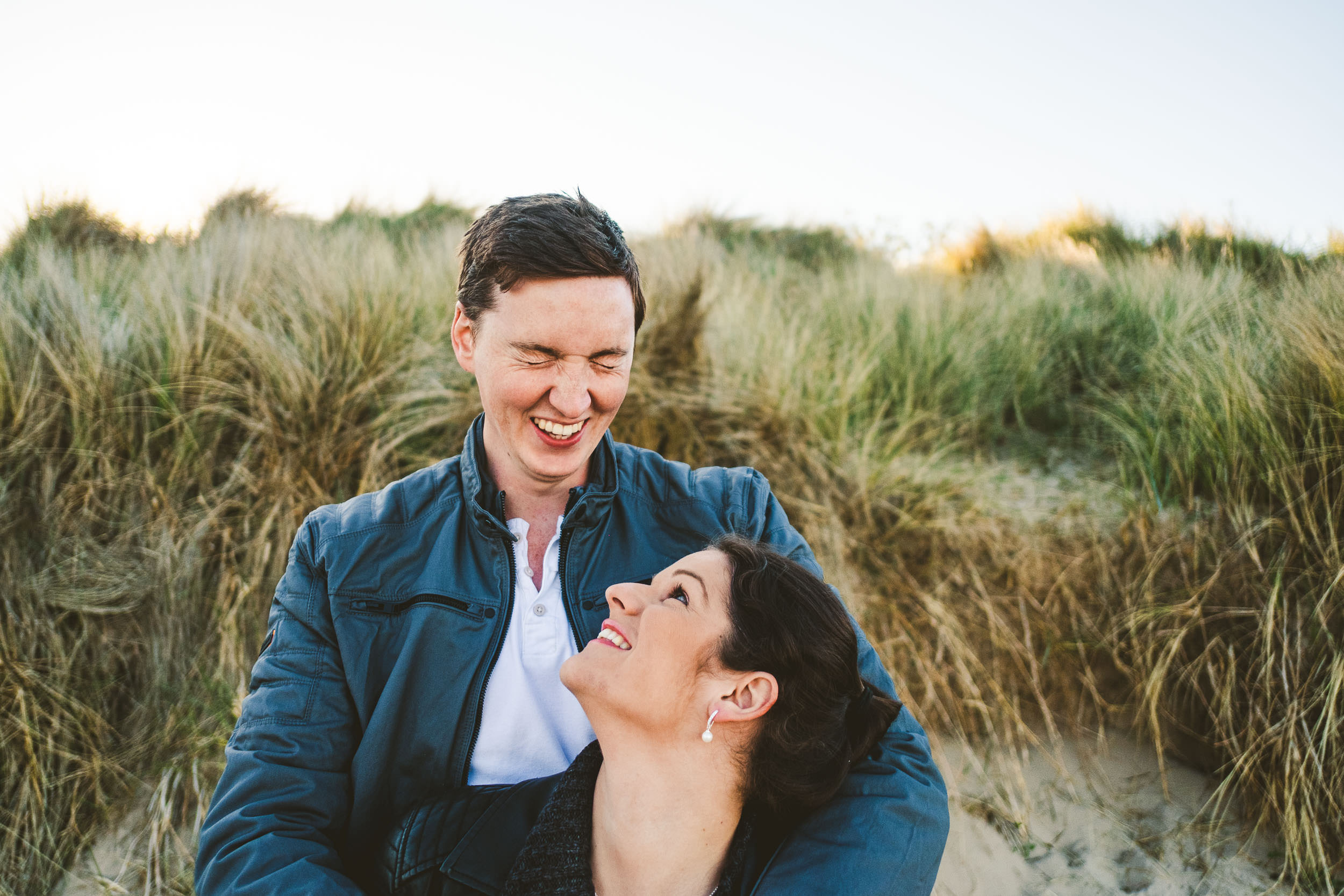 Couple laugh while standing in front of sand dunes in Northumberland