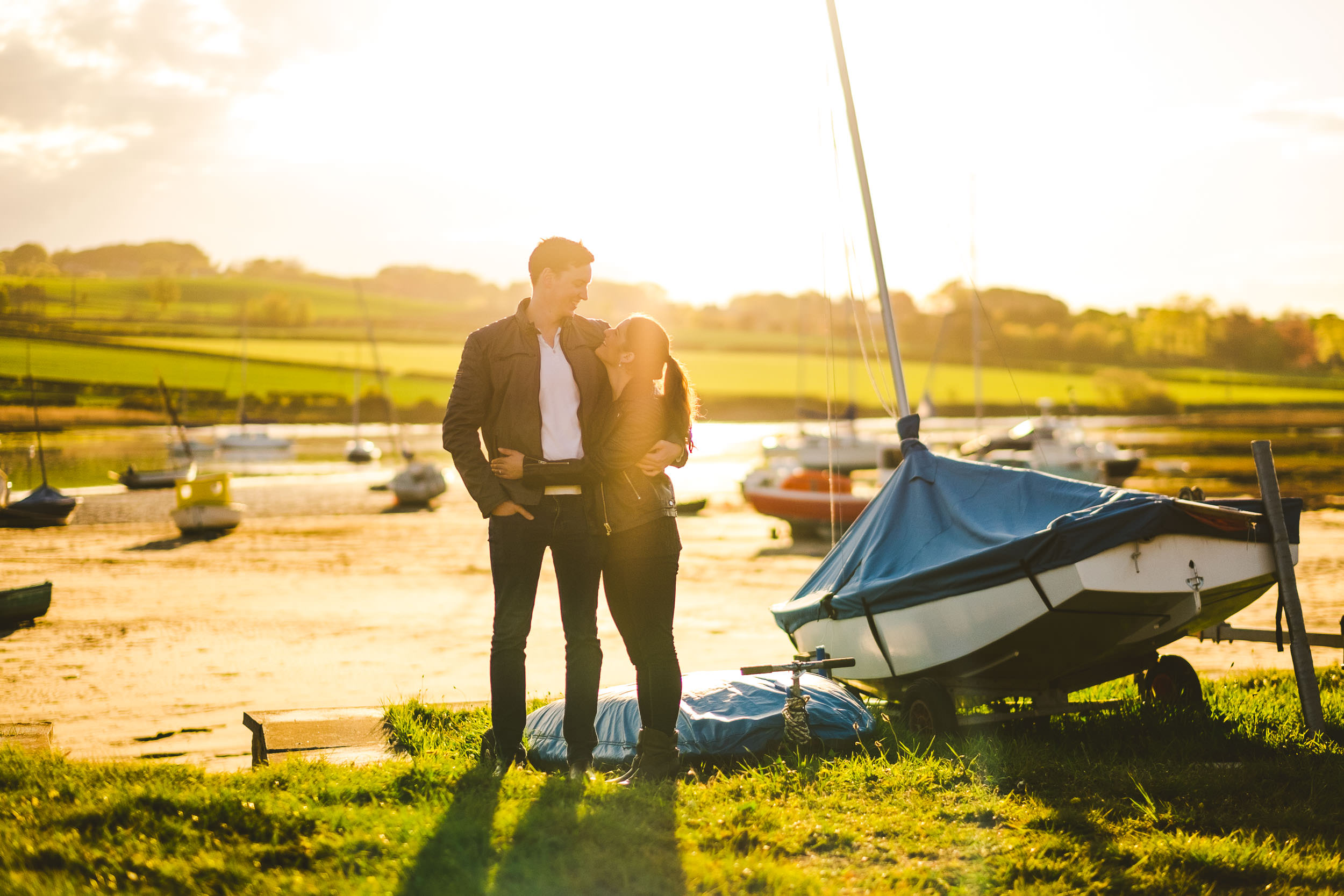Couple cuddle near colourful fishing boats in Alnmouth