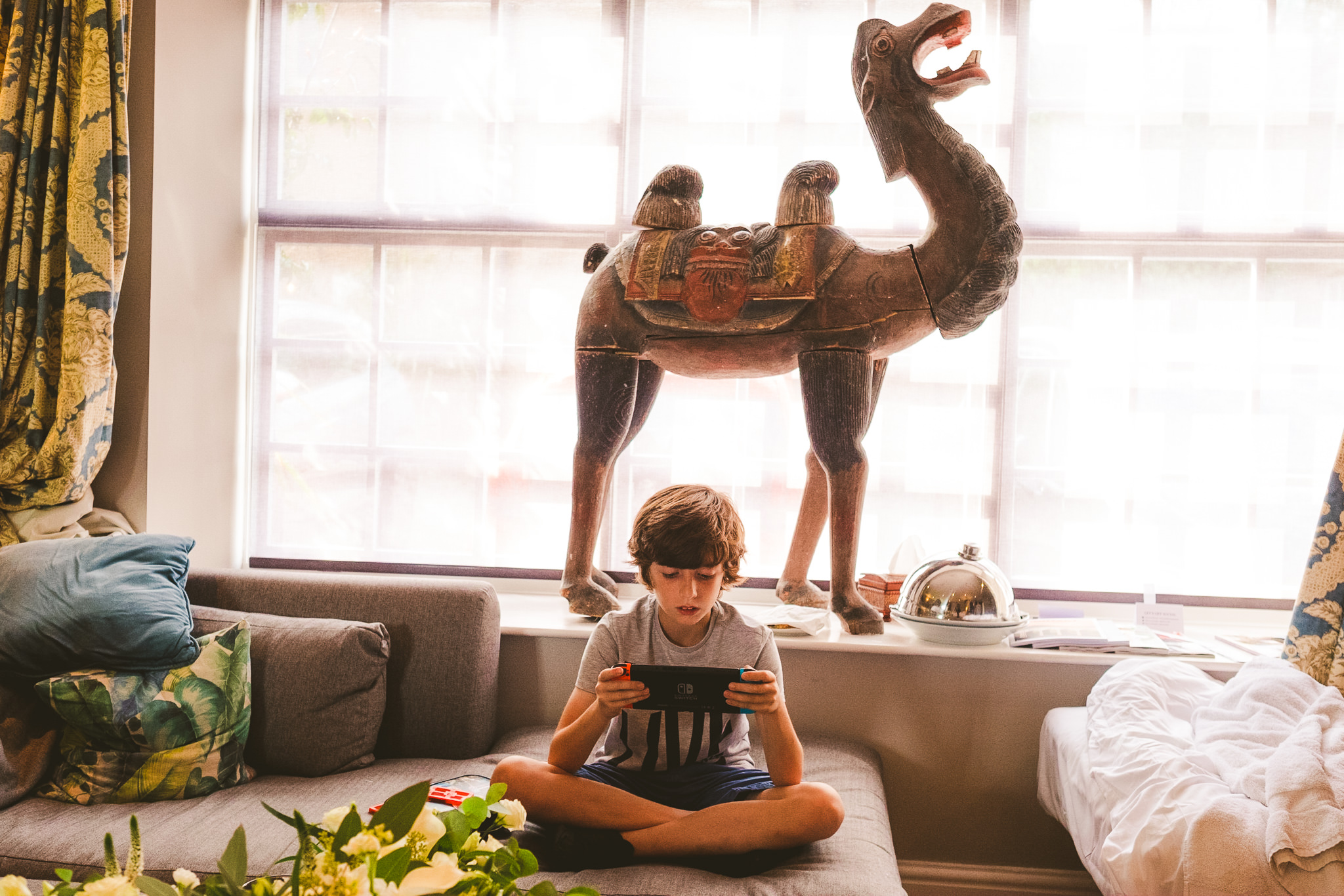 Boy plays with computer game with camel statue behind
