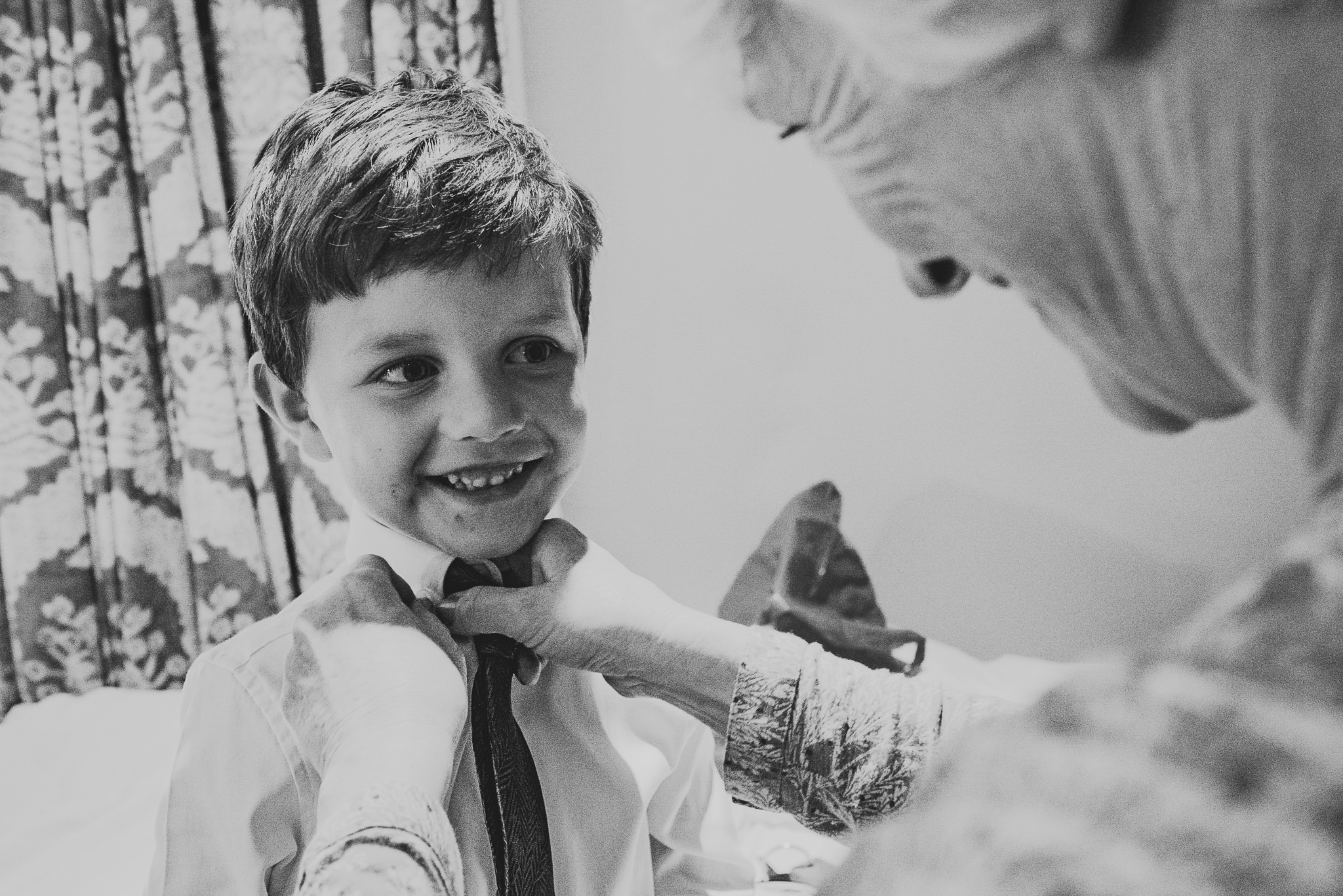 A black and white photo of the mother of the bride dressing a smiling page boy