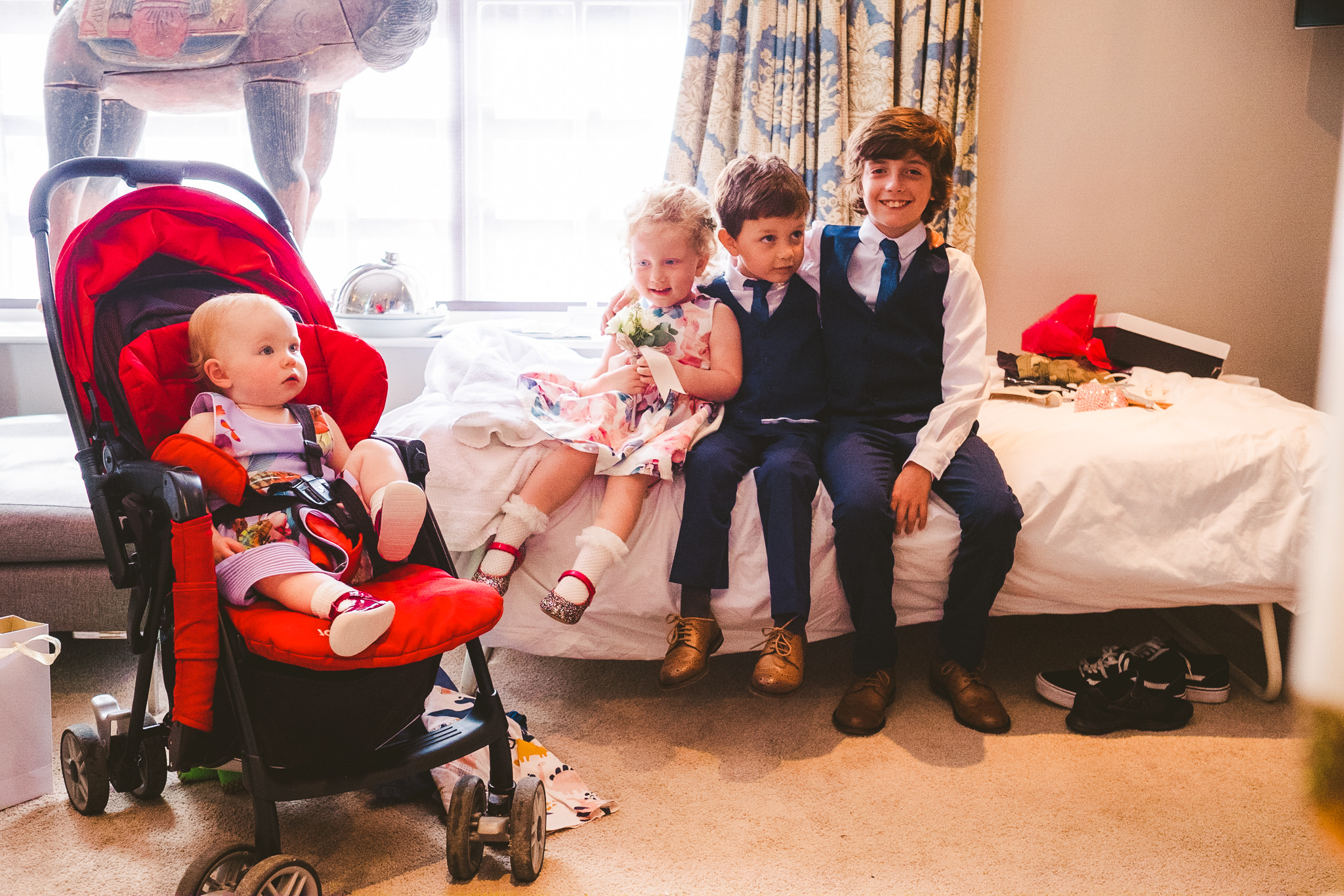 Children sitting on a bed ready for the wedding
