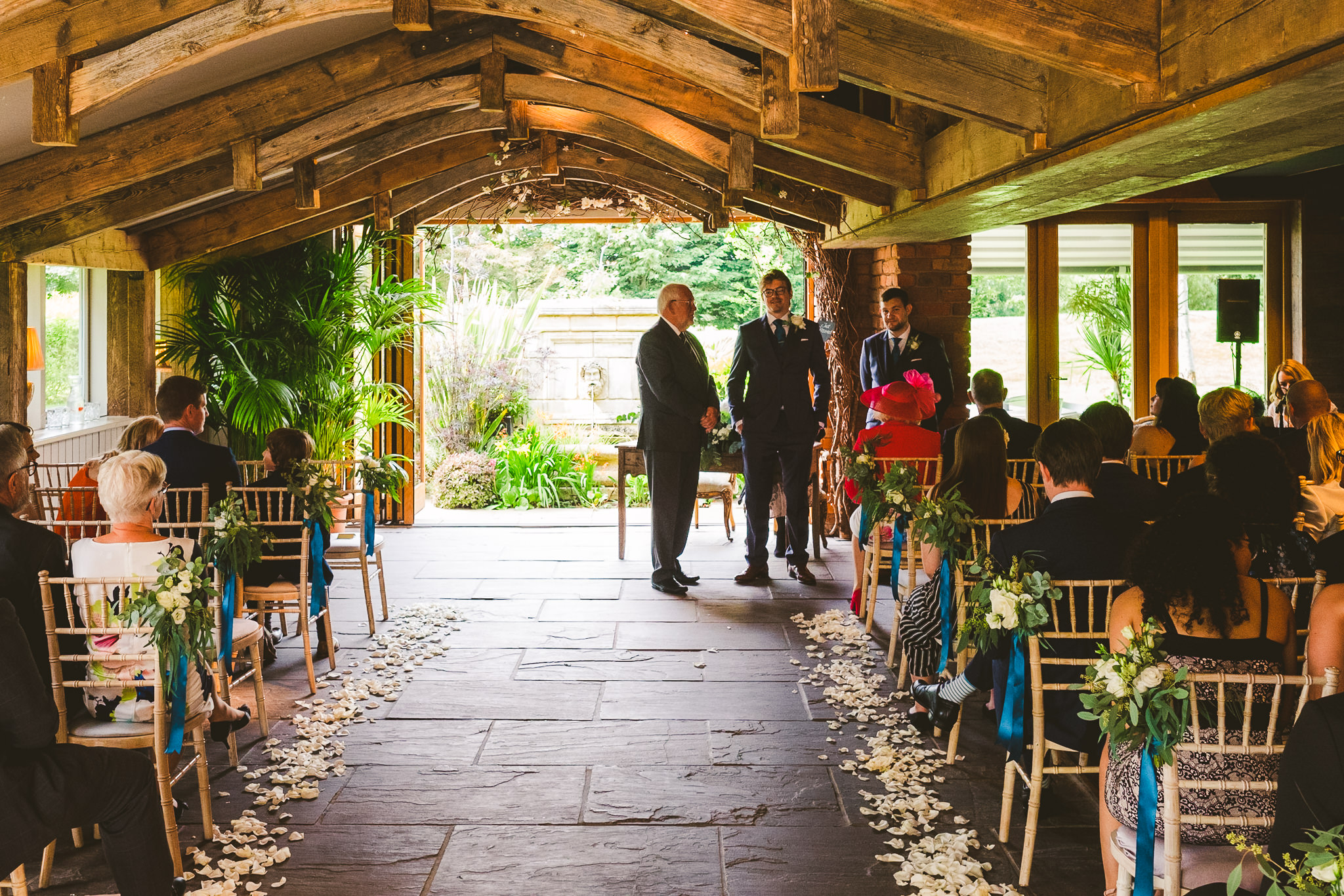 Groom waiting at the end of the aisle before his ceremony in the Garden Suite at Newton Hall