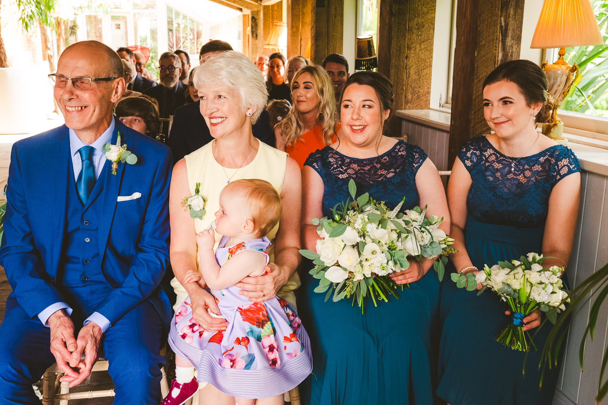The bridesmaids and the bride's family look on during the wedding