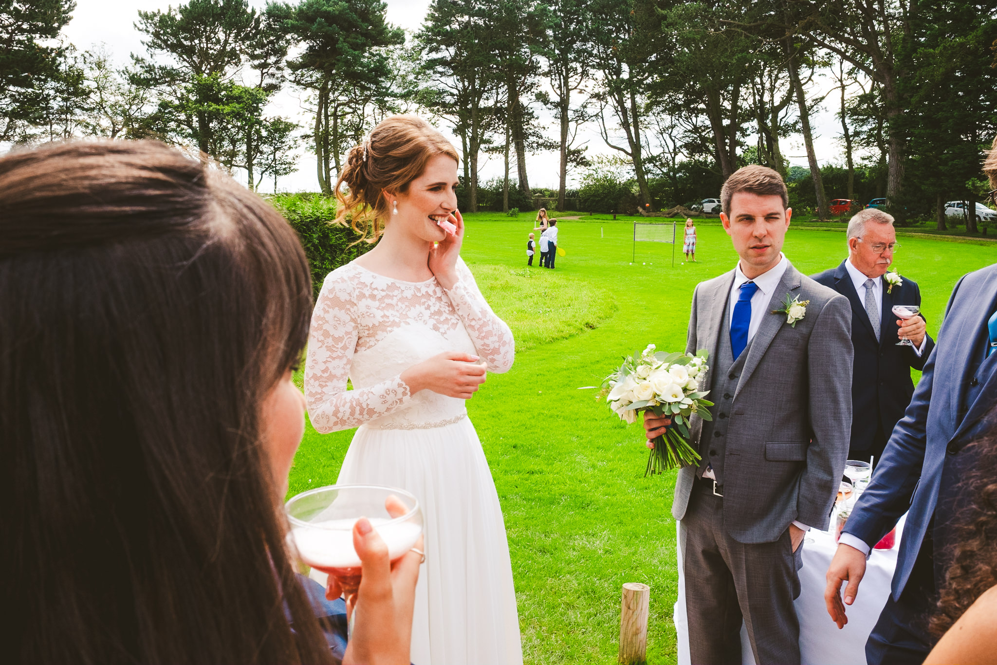 A magician entertains the bride and groom outside at Newton Hall