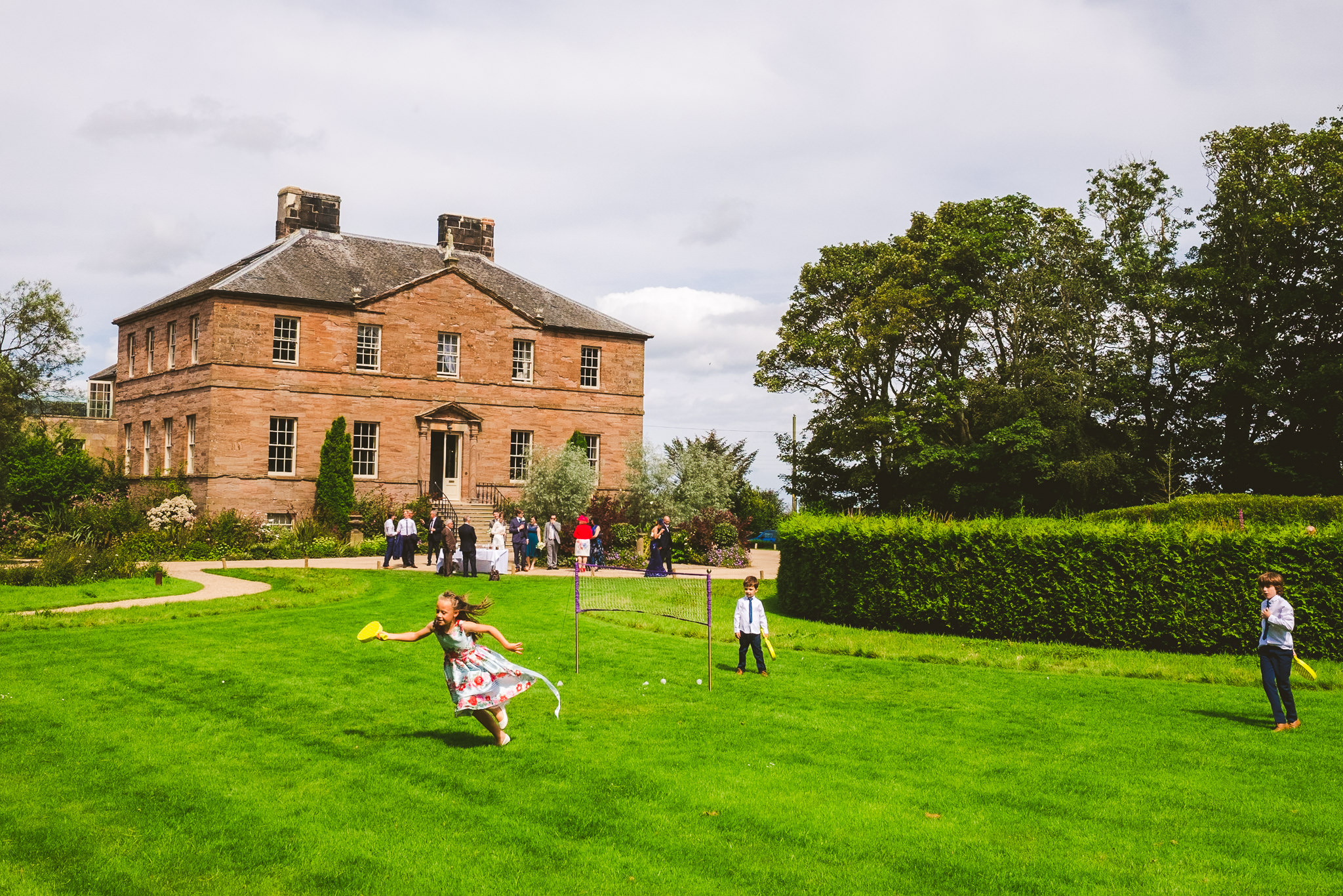 Children play lawn games with Newton Hall in the background