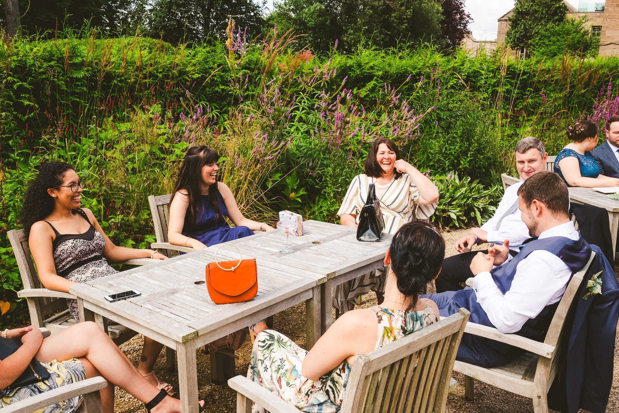 Wedding guests laugh as they sit around an outside table
