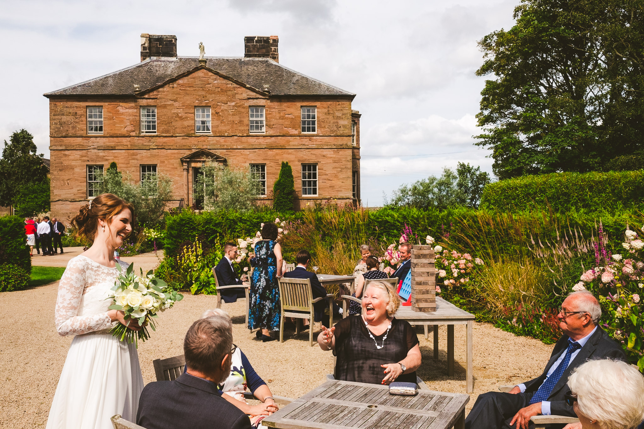 The bride talks to weddings guests with Newton Hall in the background