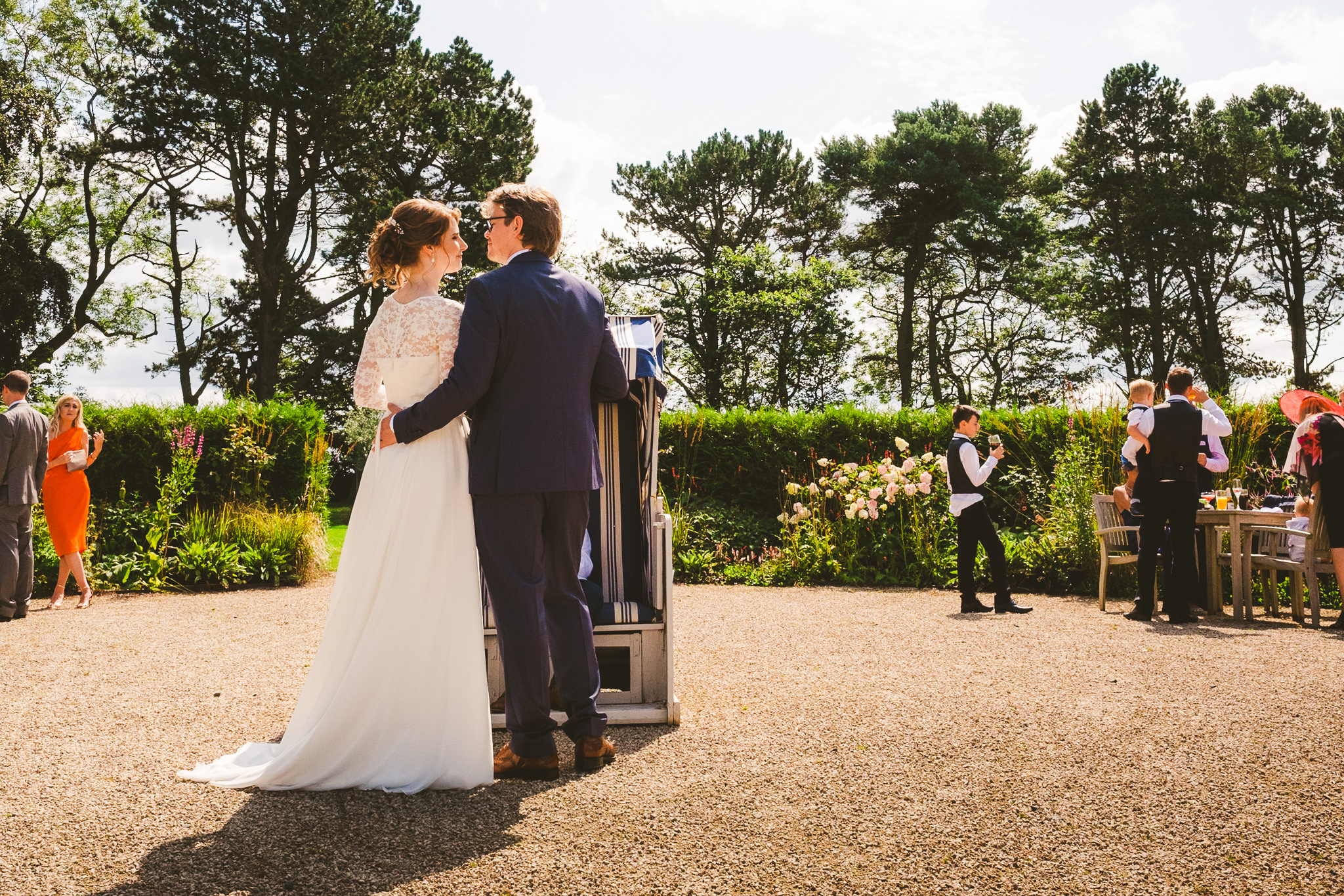 The bride and groom cuddle in the courtyard of Newton Hall
