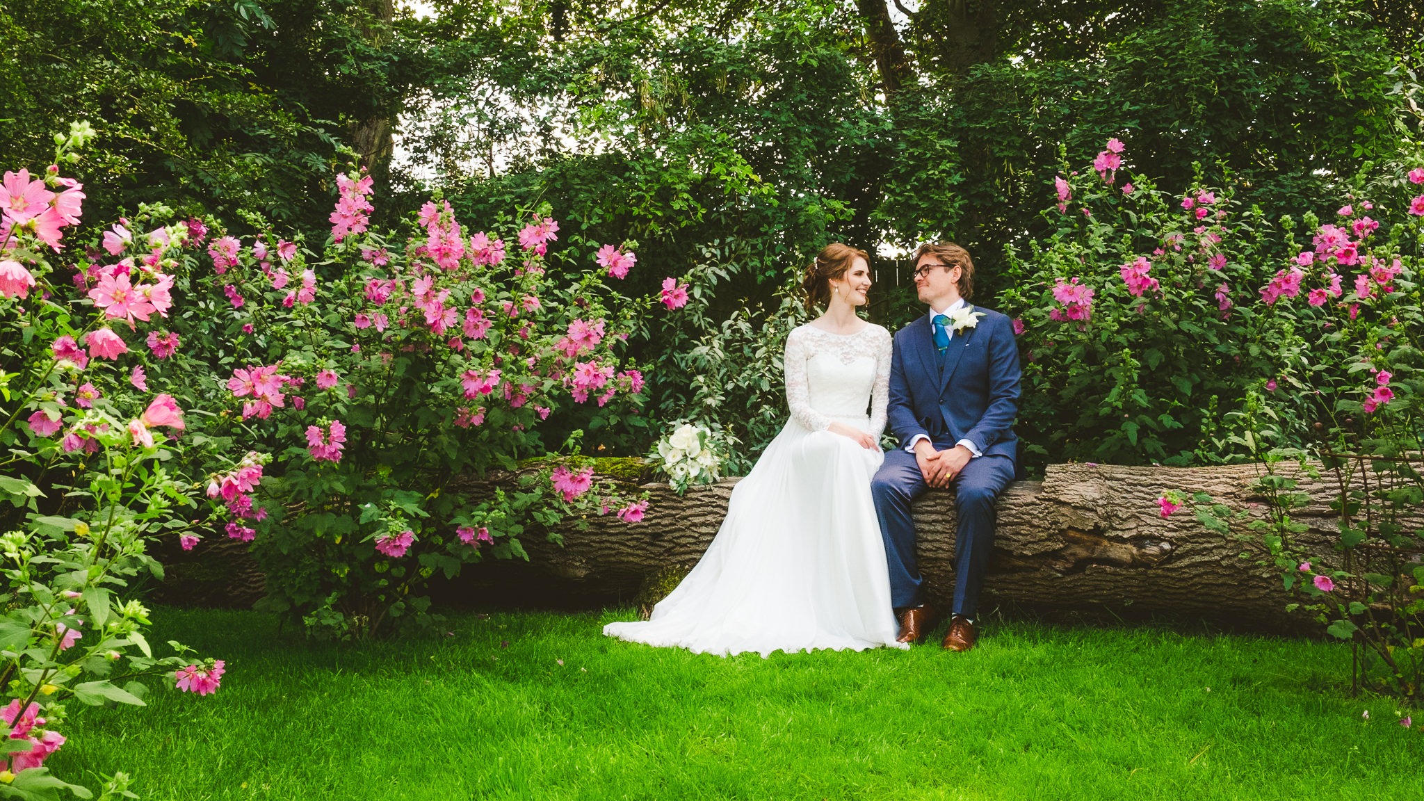 Bride and groom sit on log surrounded by flowers