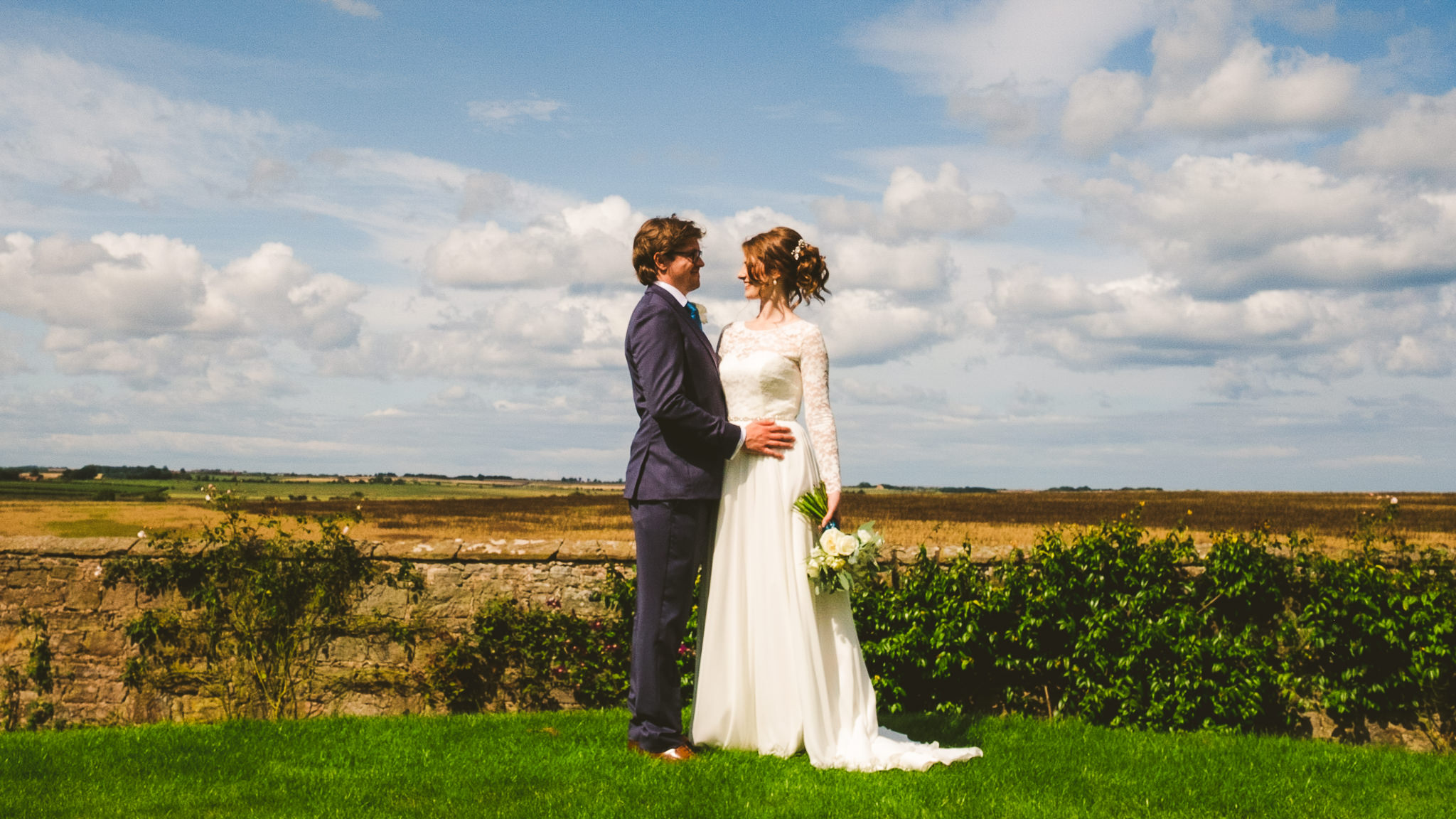 Bride and groom hold each other with the Northumberland countryside in the background