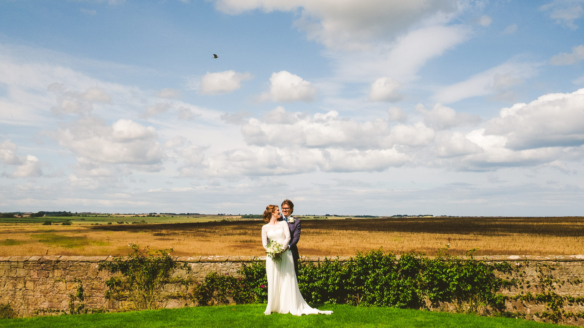 Wide view of the Northumberland countryside with bride and groom in the centre of the frame