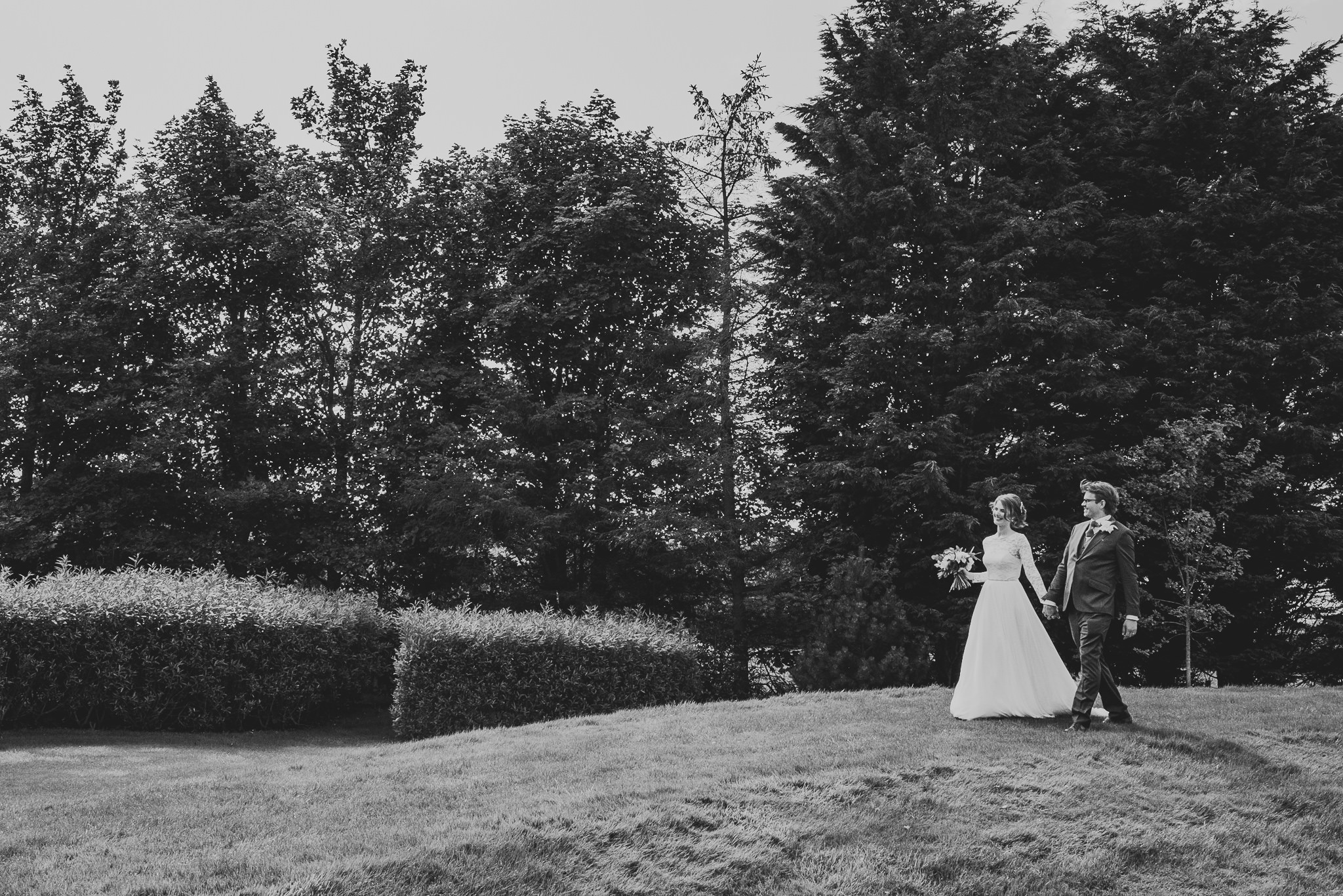 A black and white photo of the bride and groom walking through the grounds of Newton Hall
