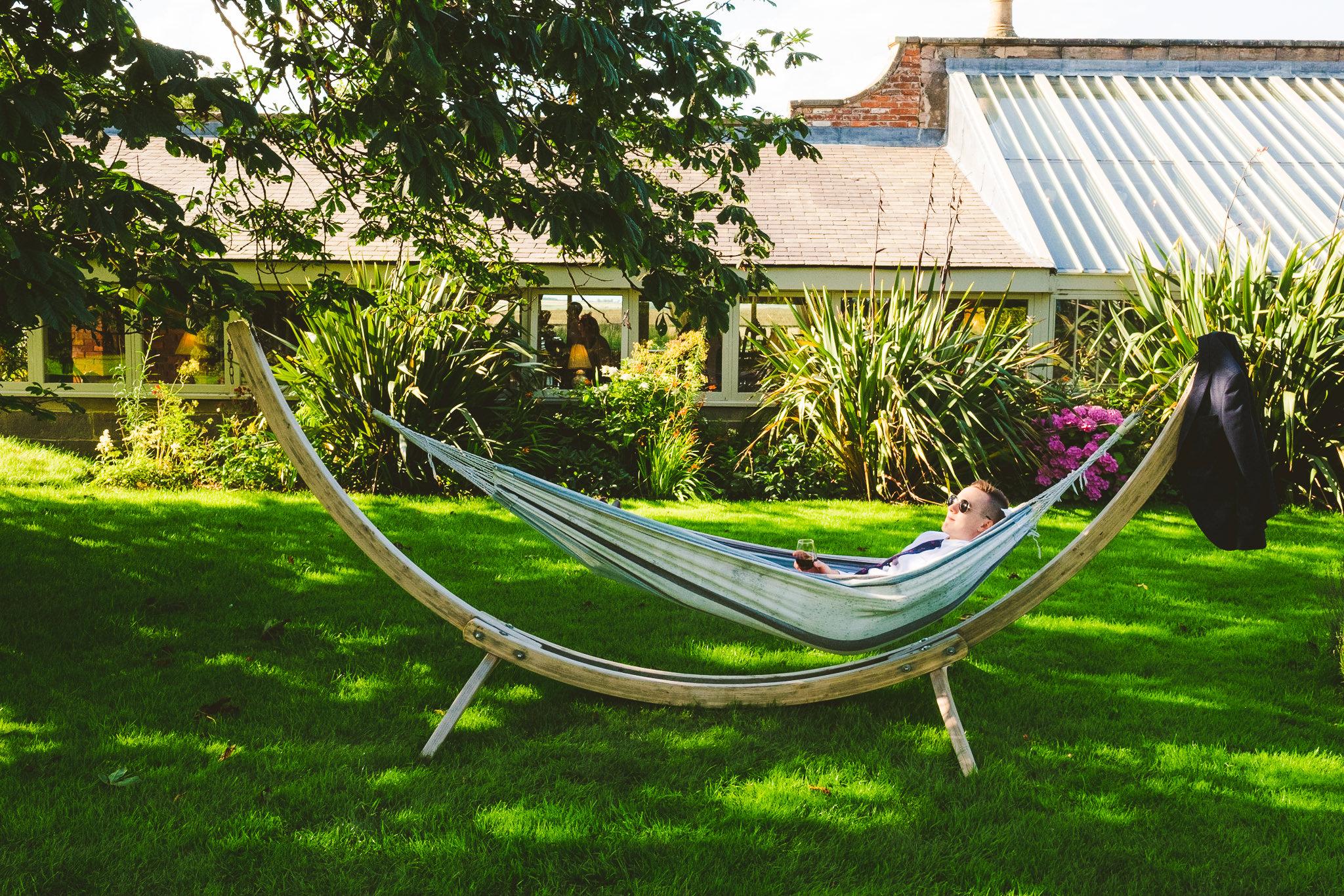 A wedding guest lies in a hammock at Newton Hall