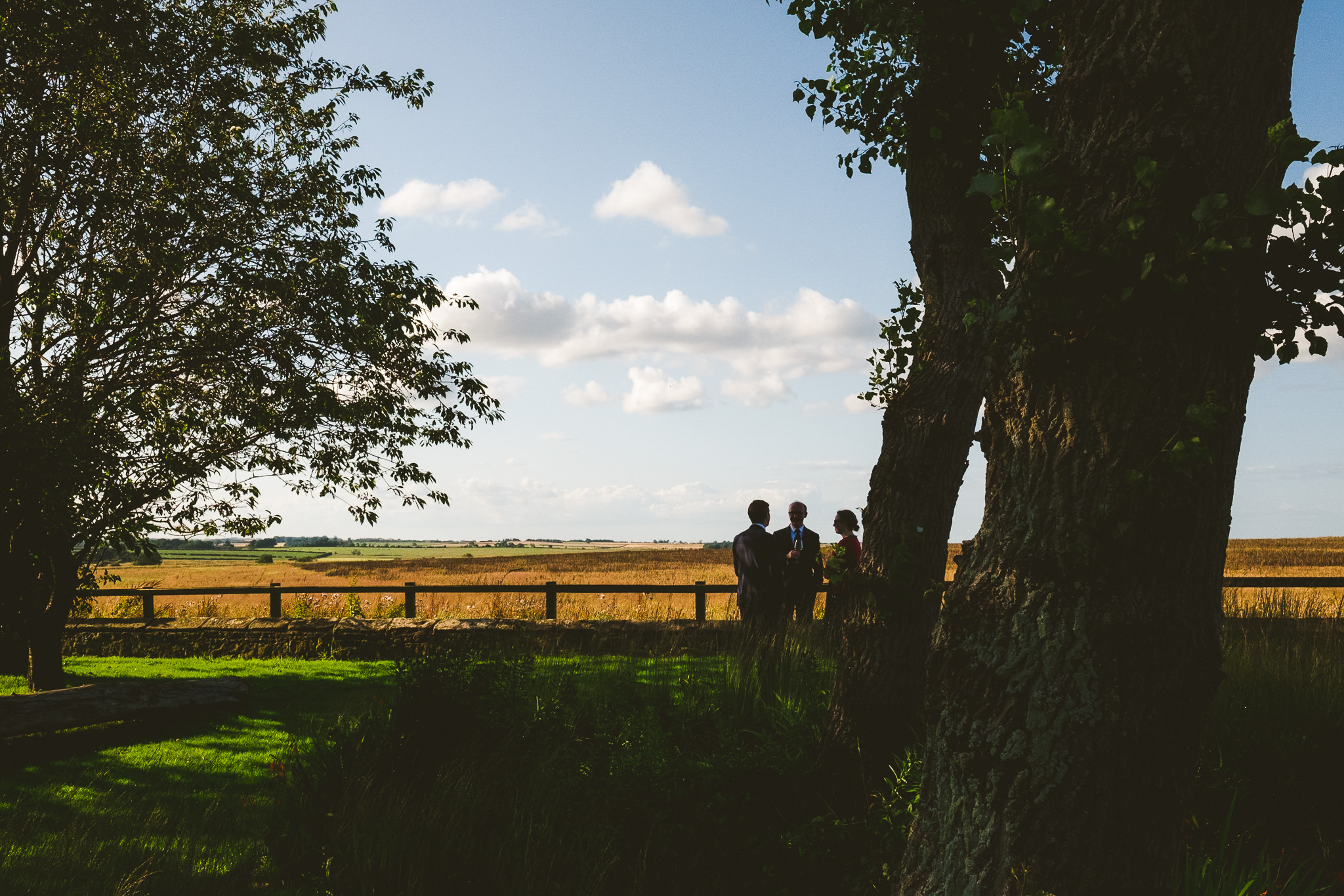 Wedding guests silhouetted against the sky at Newton Hall