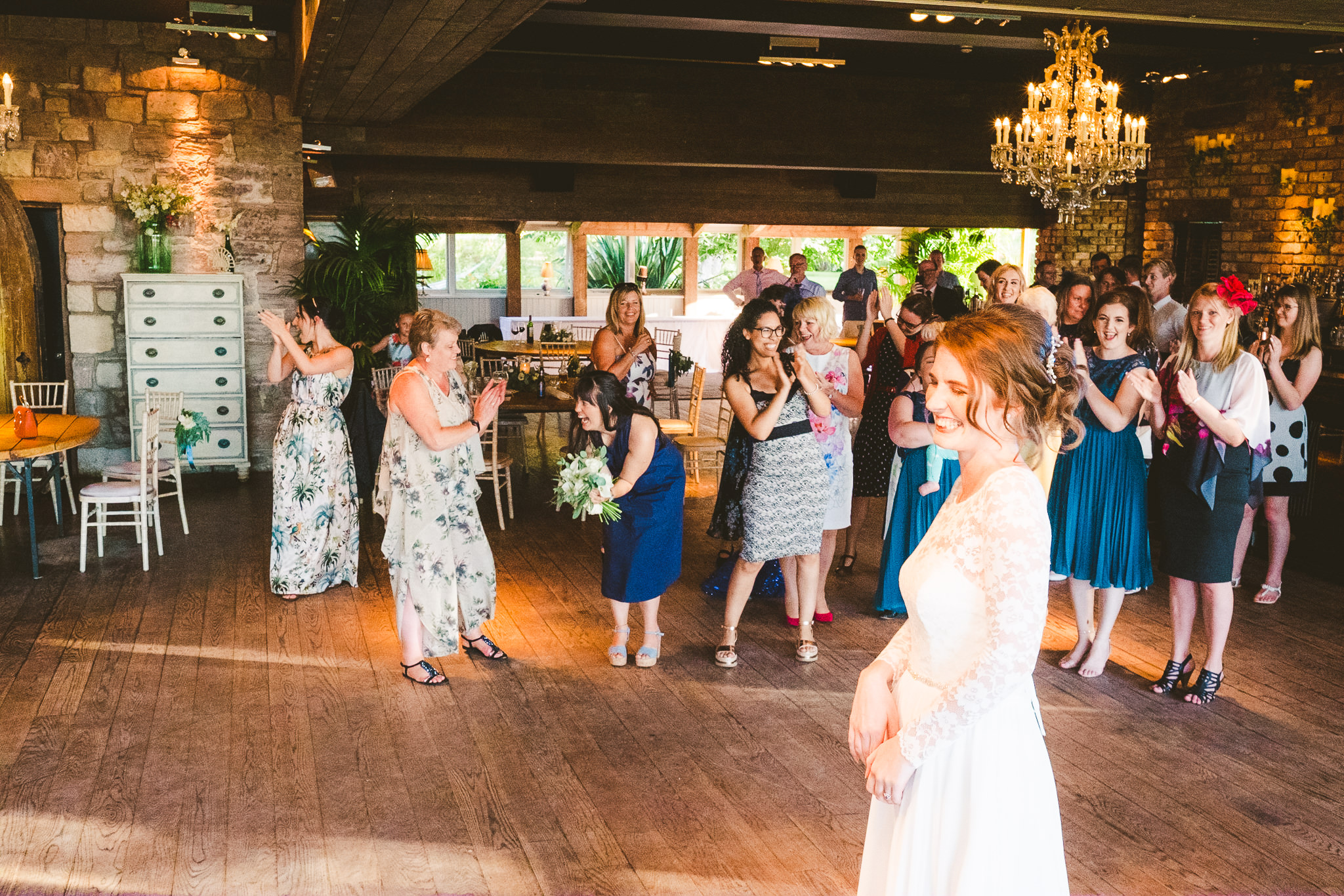 Guest catches the bouquet after the bouquet toss at Newton Hall