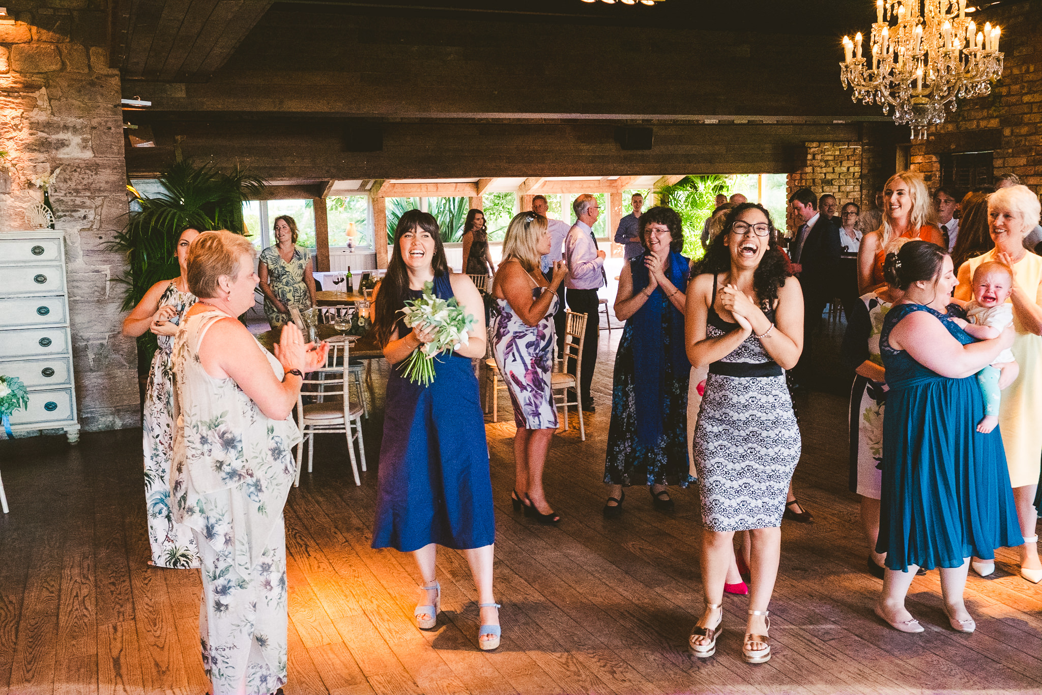 Guests laugh after the Bouquet toss at Newton Hall