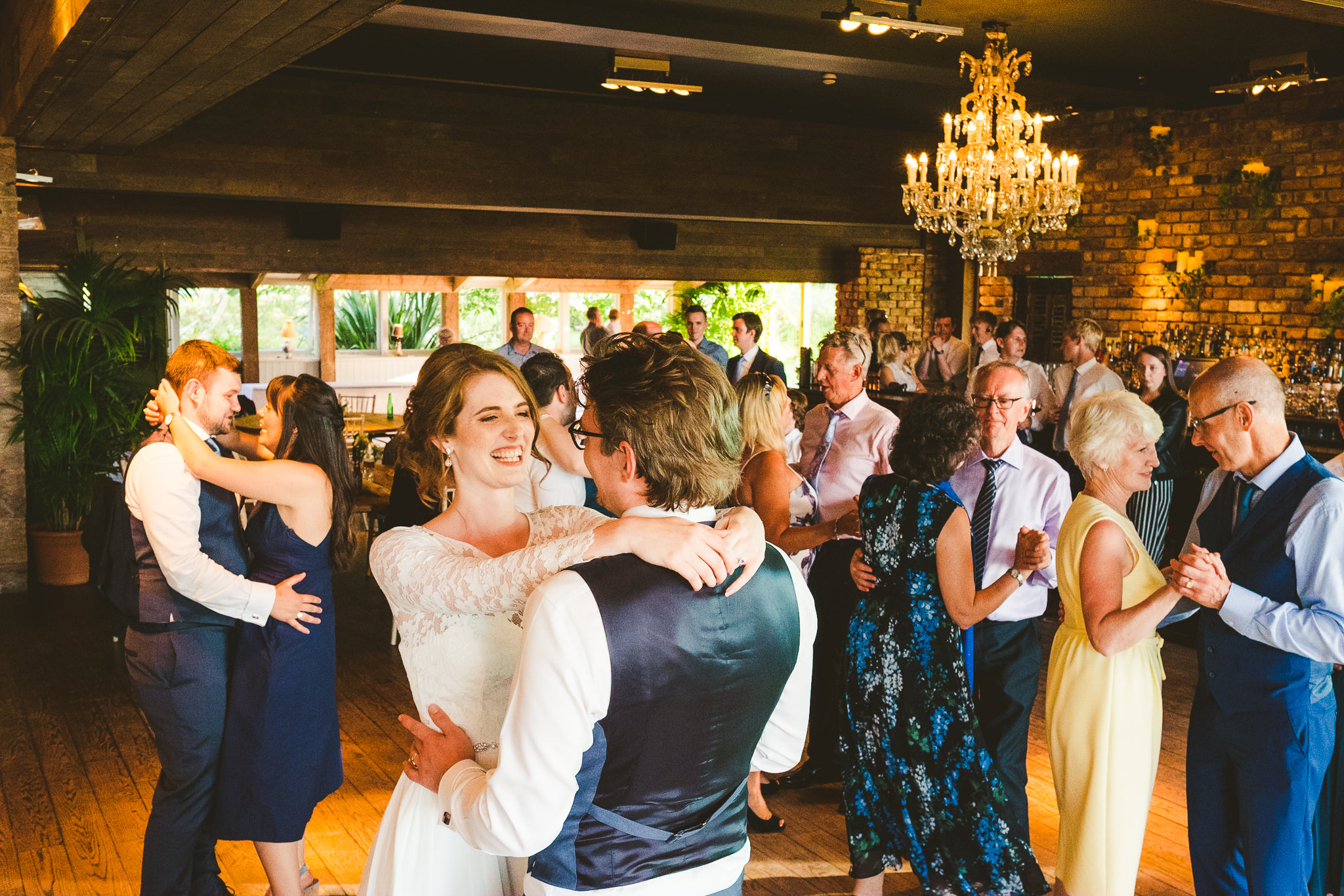 Bride and groom first dance at Newton Hall as guests look on
