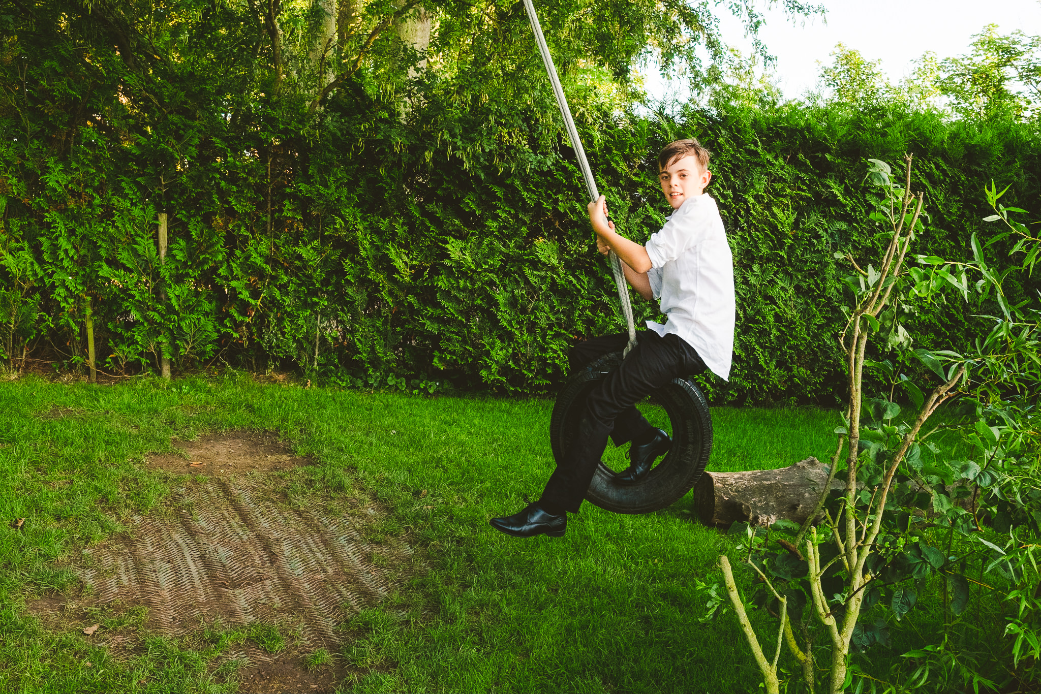 Boy plays on tyre swing at Newton Hall