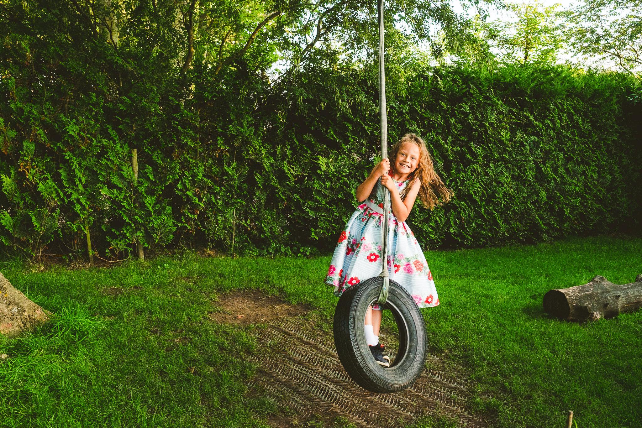 Girl swings on rope swing at Newton Hall