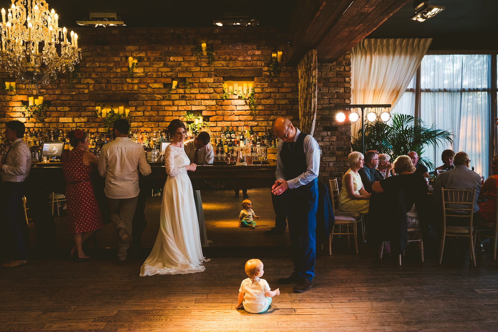 Bride watches baby crawling on floor at bar in Newton Hall