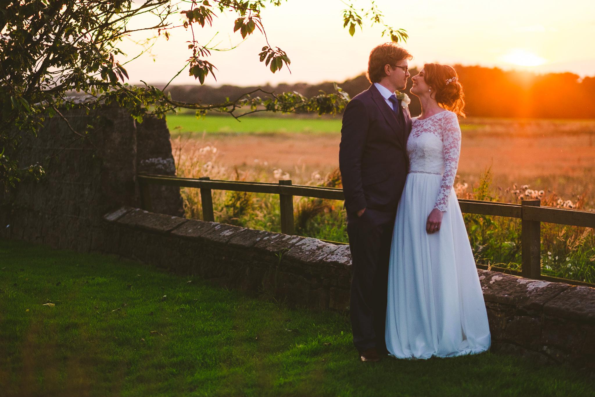 Bride and groom kiss at sunset at Newton Hall