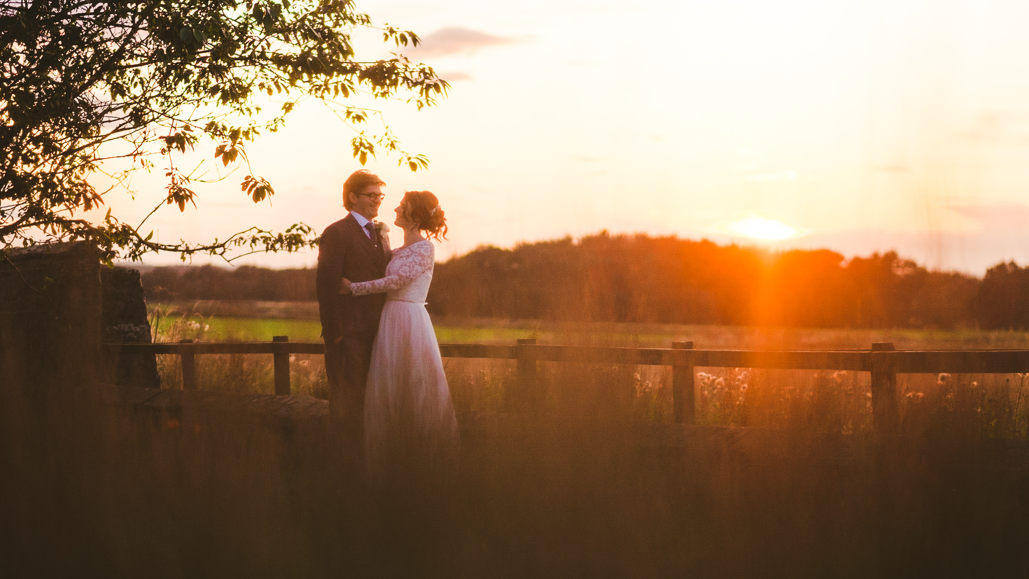Bride and groom cuddle at sunset at Newton Hall