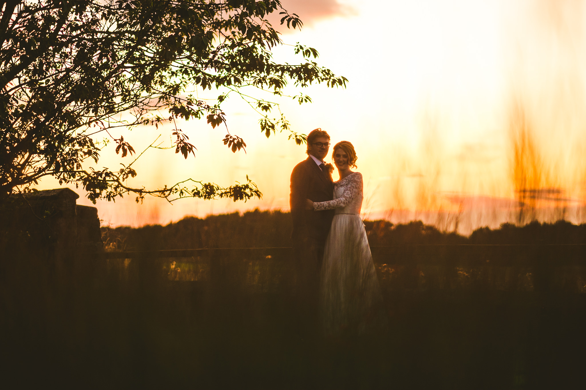Bride and groom hold each other at sunset at Newton Hall