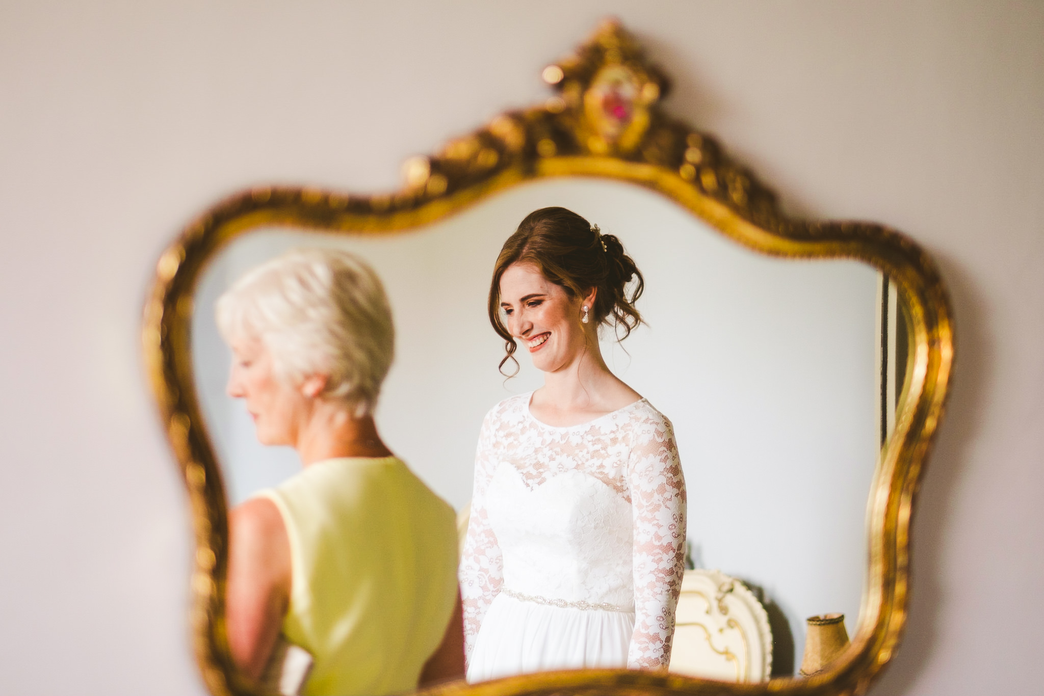 Bride and her mother reflected in a mirror before the ceremony