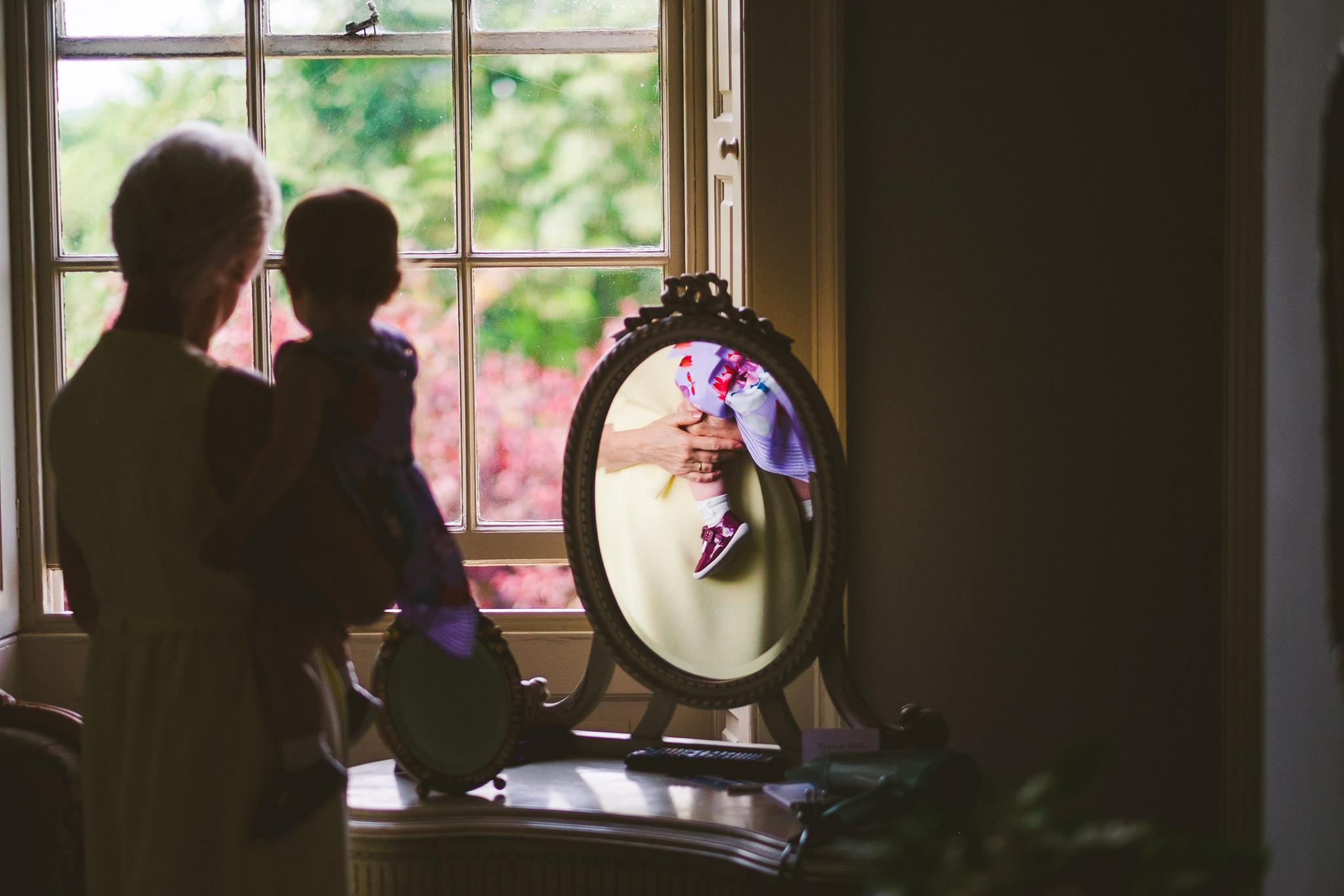 Mother of the bride holds the bride's daughter while looking out of the window