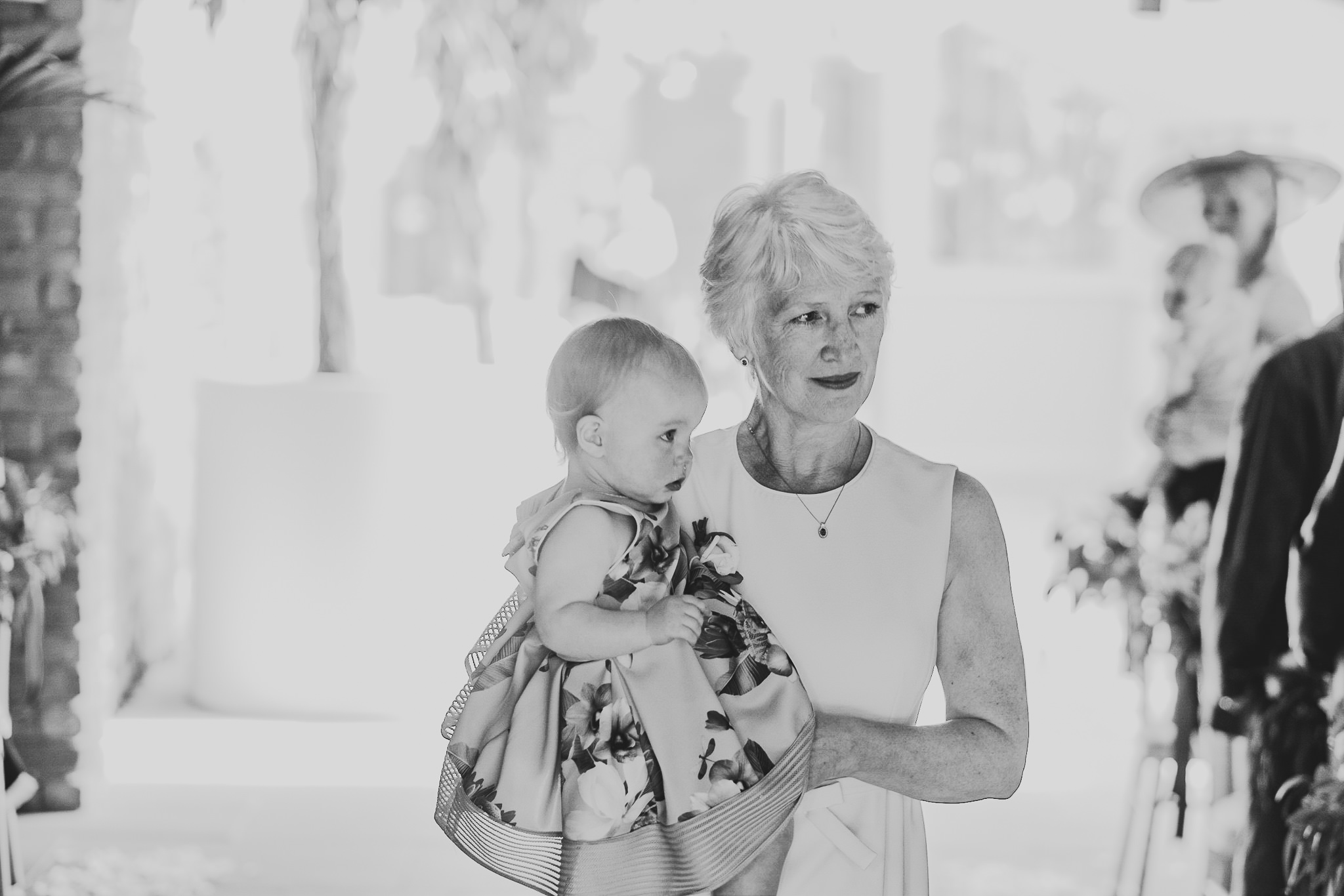 A black and white photo of the mother of the bride carrying in the bride's daughter to the ceremony