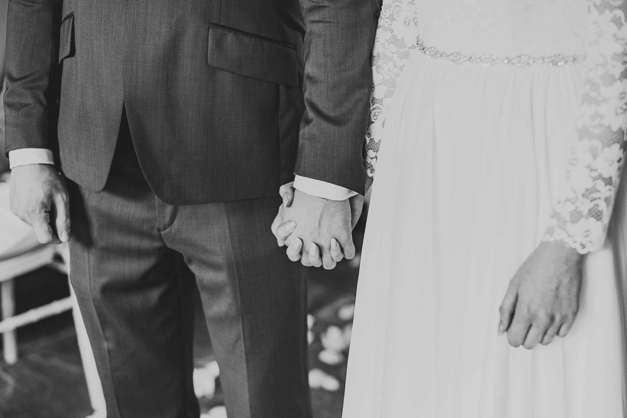 A black and white photo of the bride and groom holding hands during their wedding ceremony