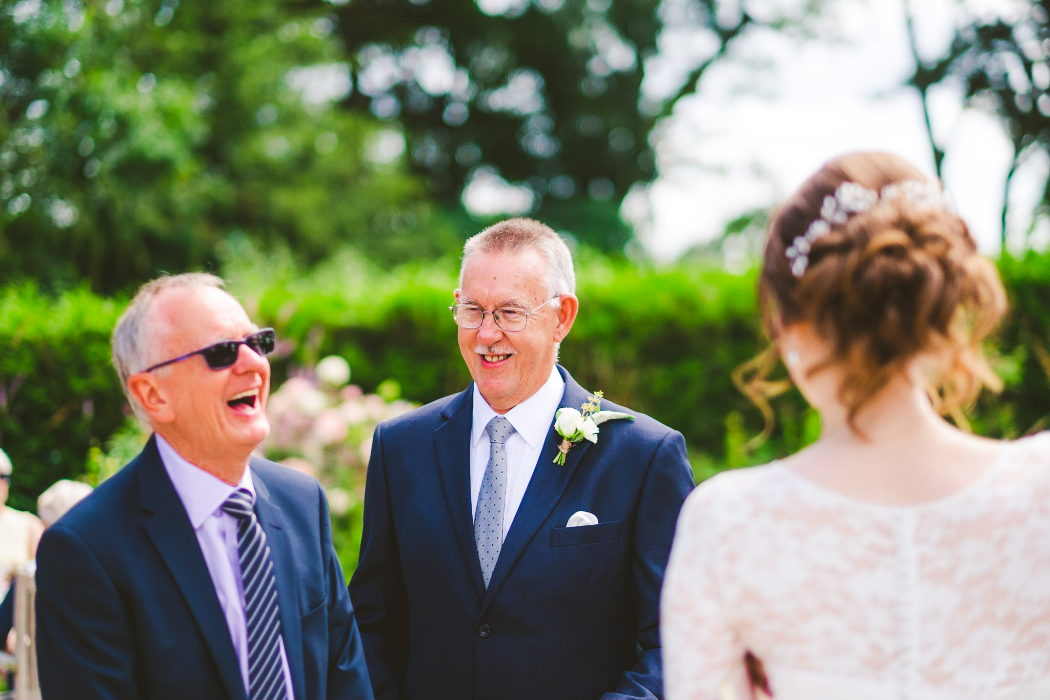 Wedding guests laugh while relaxing outside