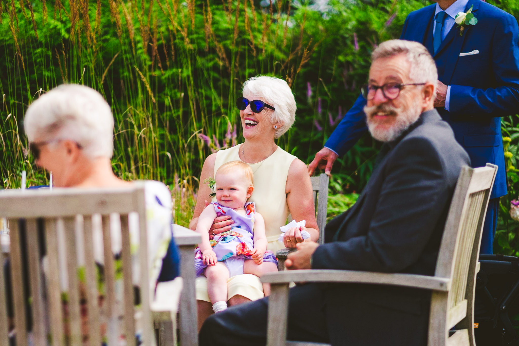 The mother of the bride enjoys a joke while sitting in the sun