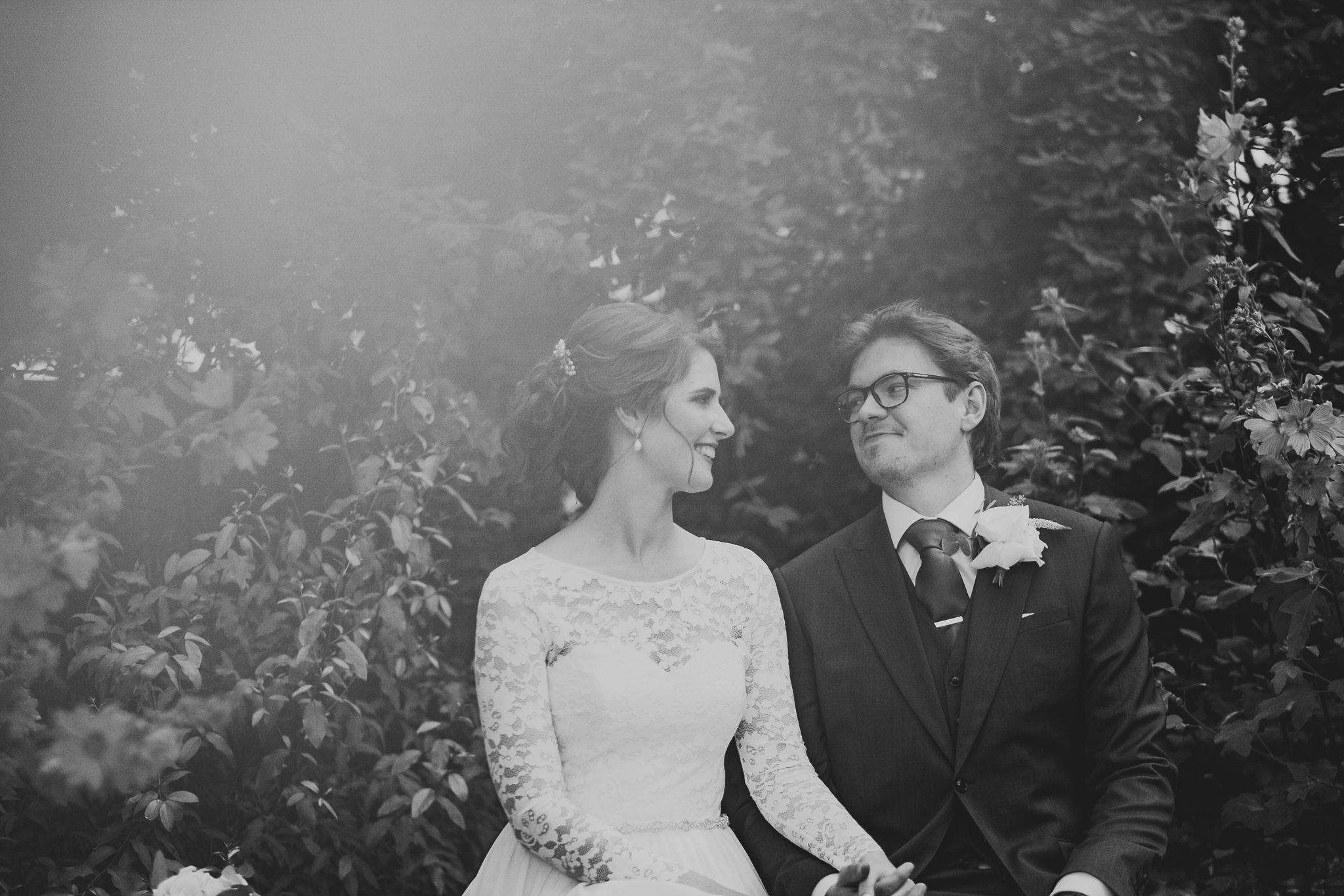 A black and white photo of the bride and groom laughing with intense sun flare coming from above