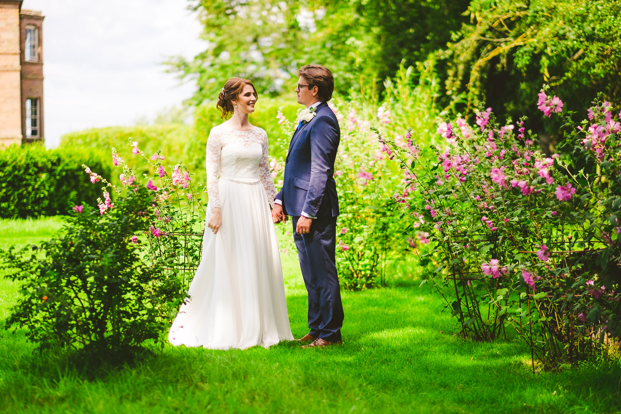 Bride and groom hold hands in the colourful gardens of Newton Hall