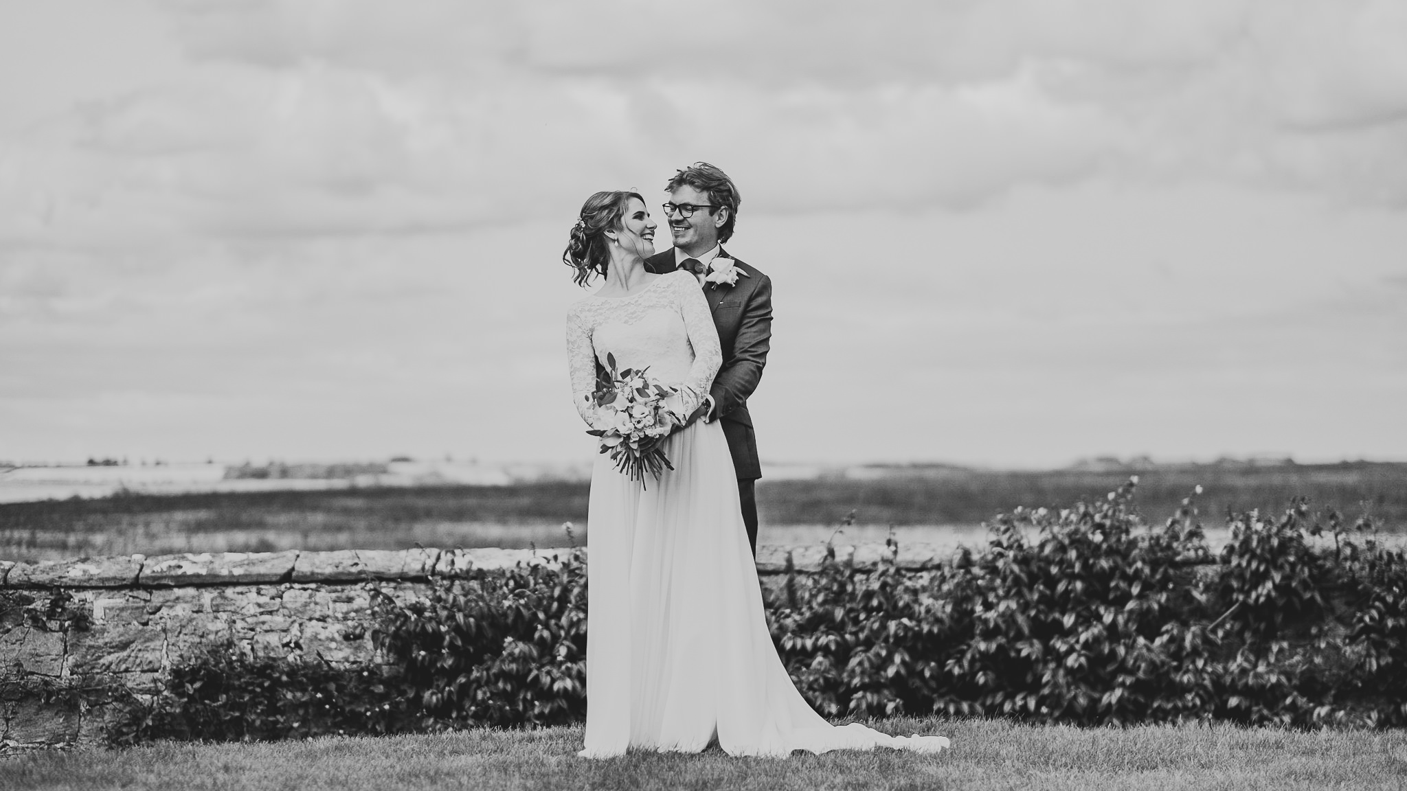 A black and white photo of the bride and groom cuddling with Northumberland countryside behind