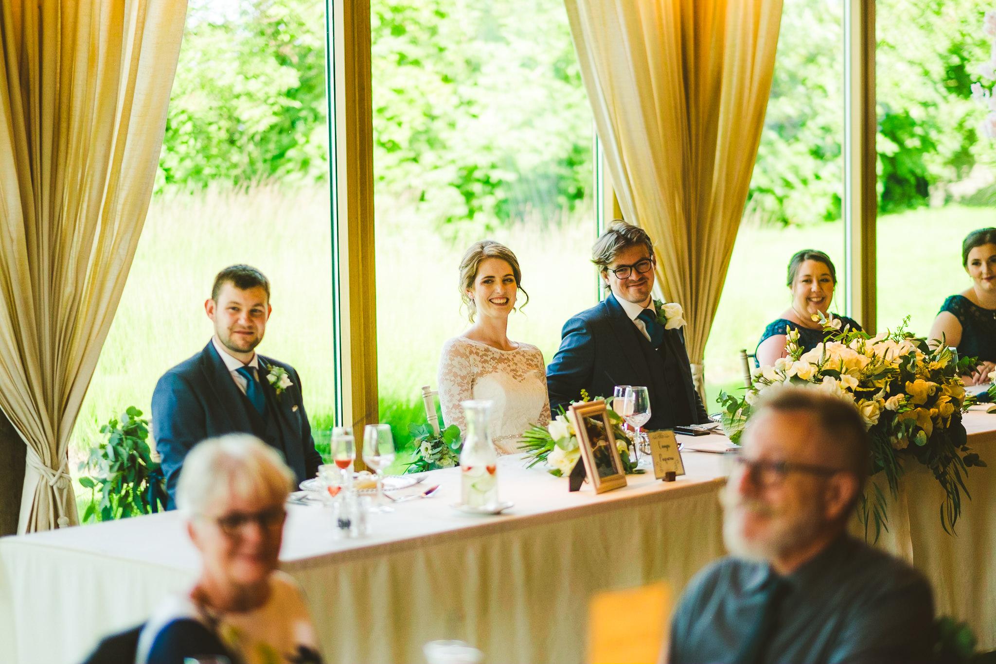 Bride and groom laugh at wedding speech