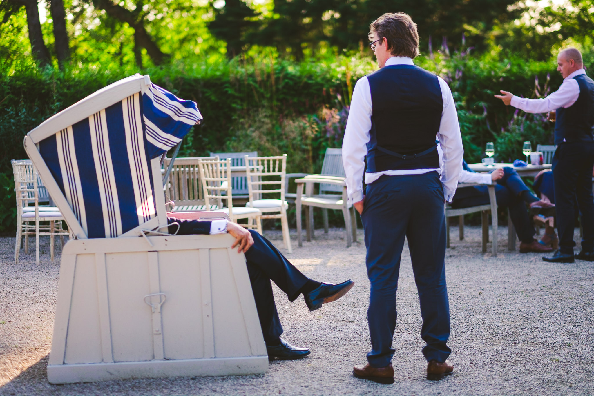 The groom chats to a guest who is sitting in a fabric covered chair