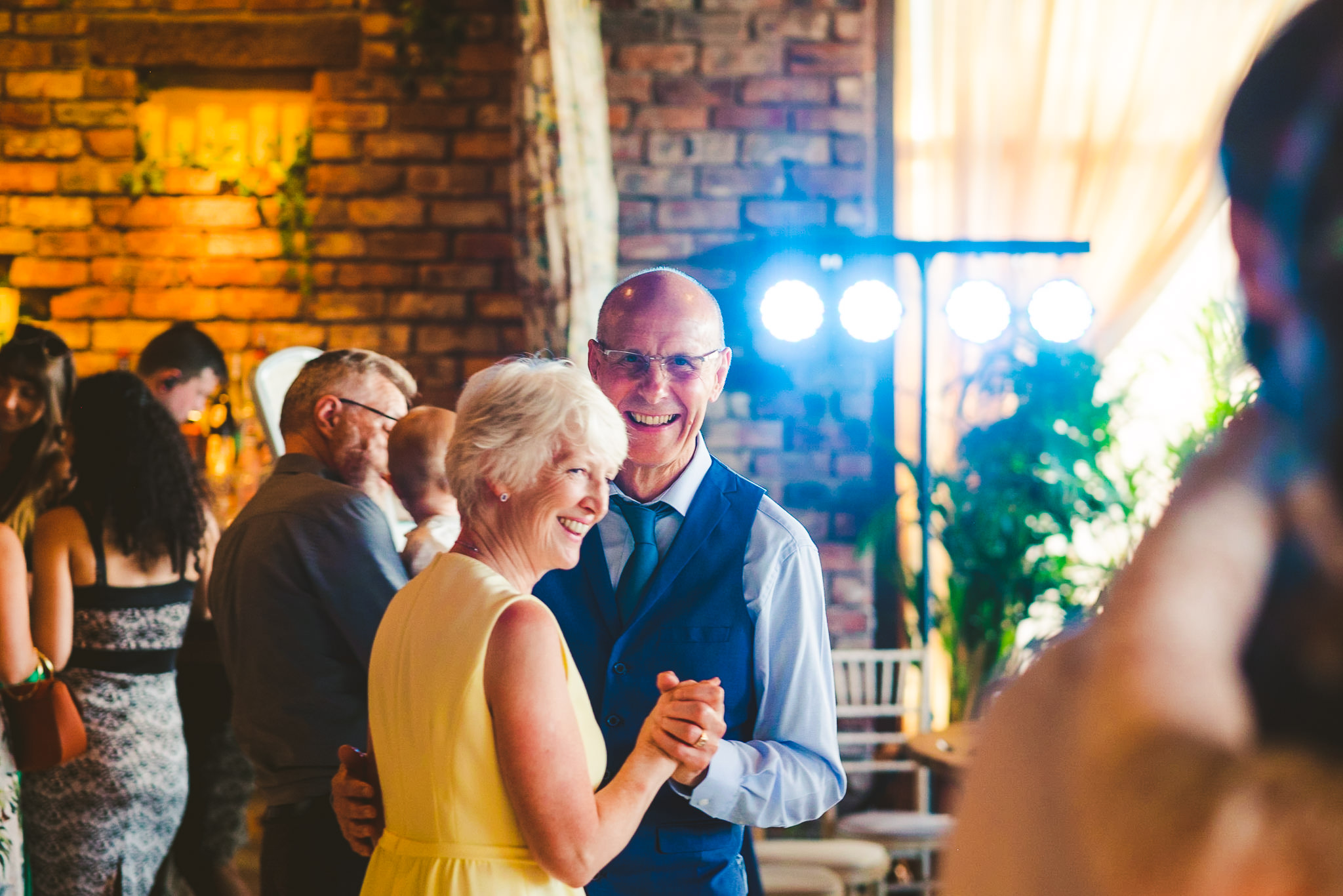 Mother and father of the bride look on during bride and groom first dance at Newton Hall