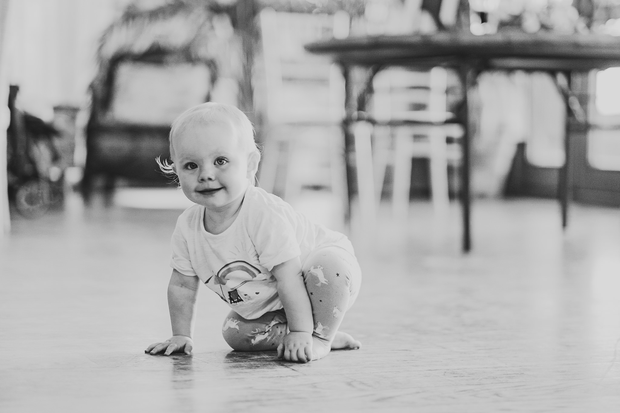 A black and photo of a baby crawling on the dance floor