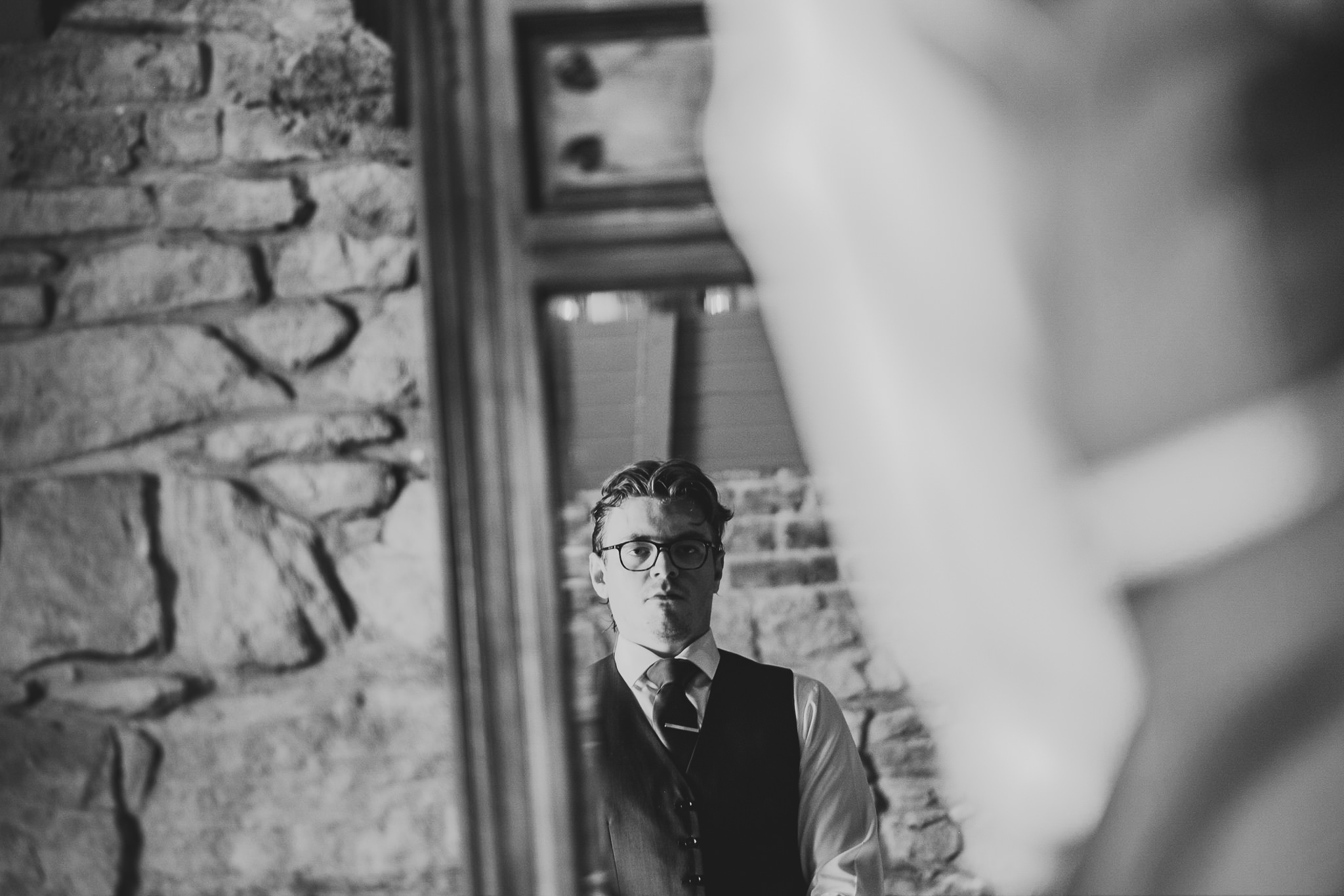 A black and white photo of the groom getting ready