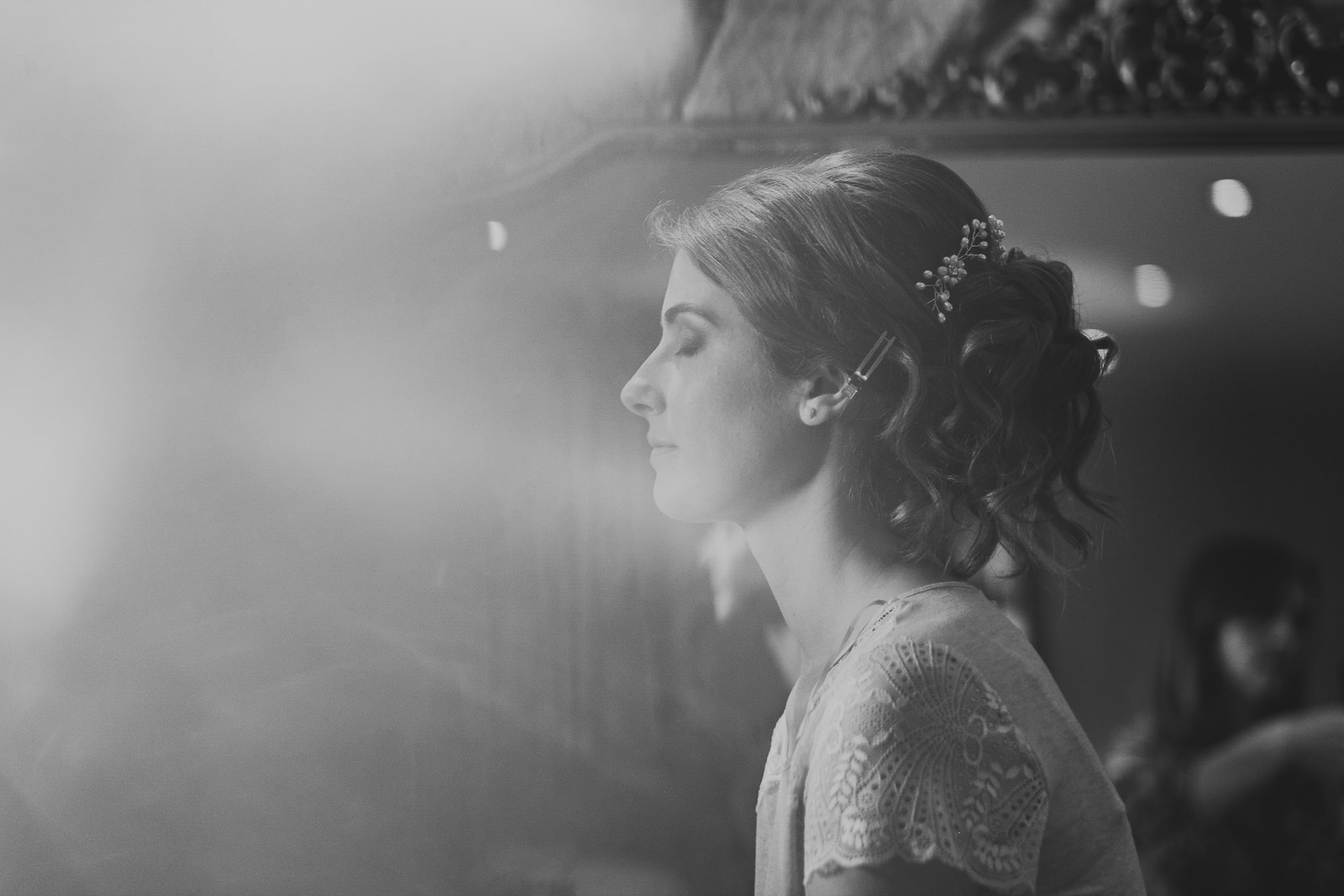 A black and white photo of the bride having make up applied