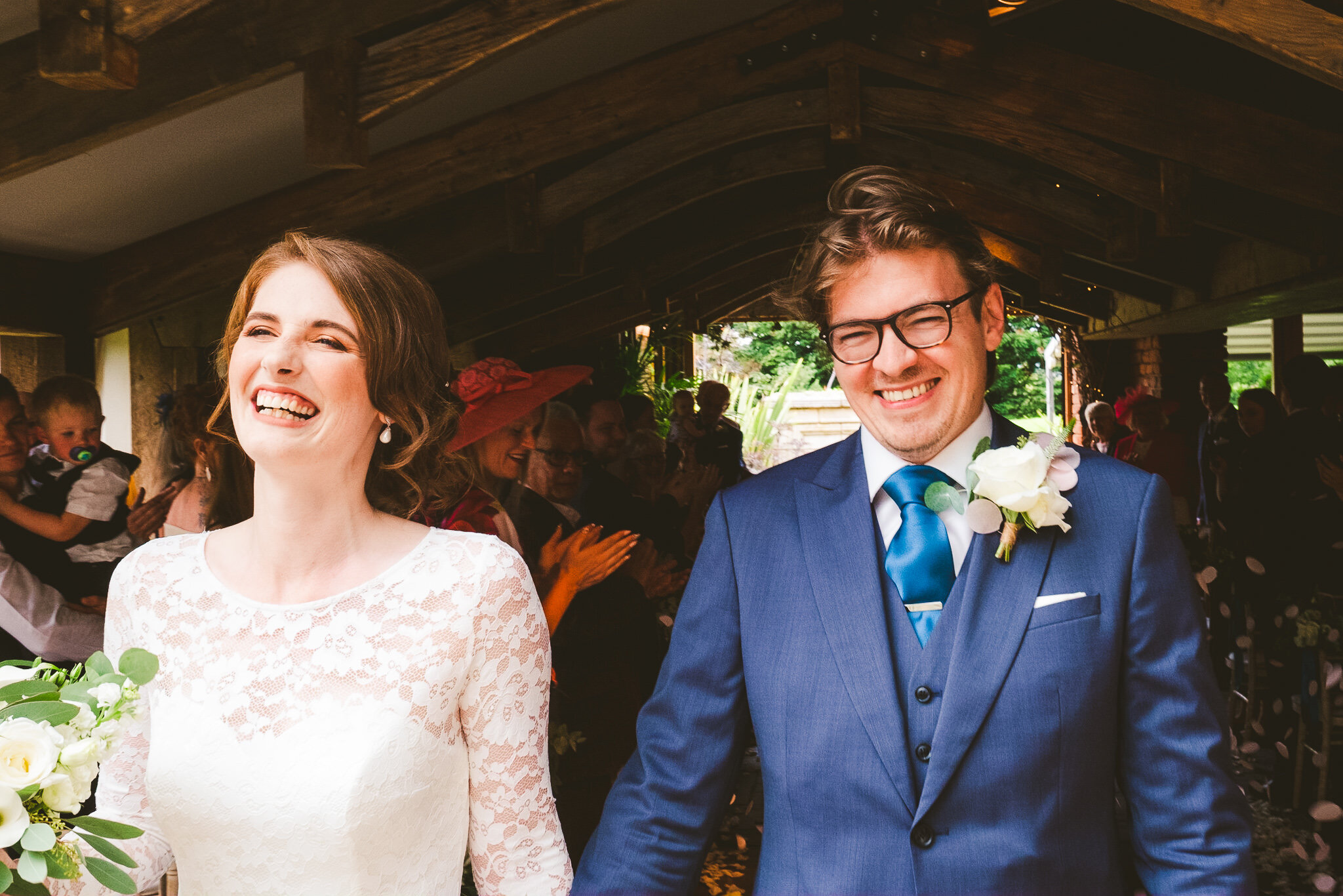 Alice and Andrew have the biggest smiles as they emerge from their wedding ceremony at Newton Hall in Northumberland
