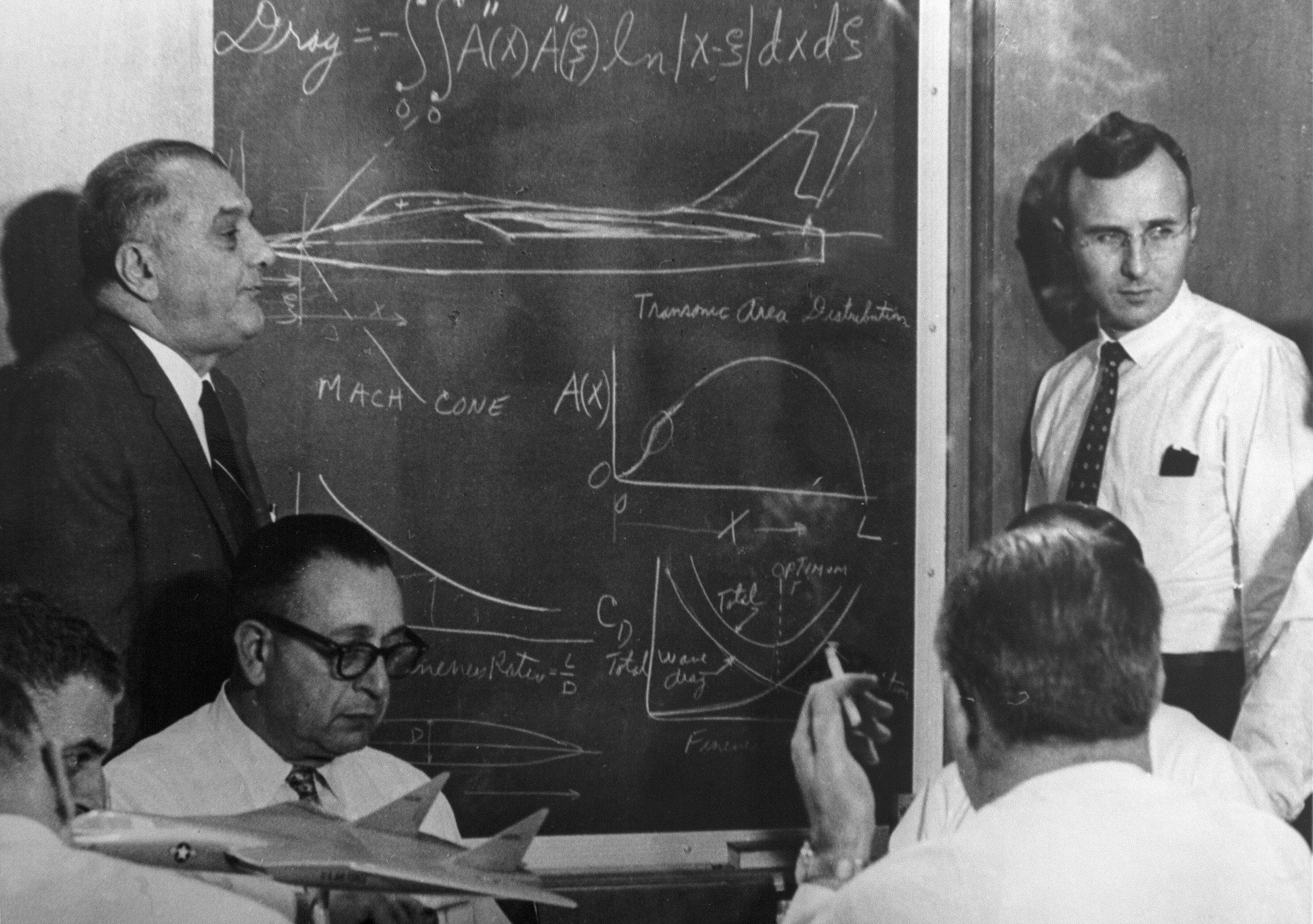 Kartveli (standing left) illustrates his aviation designs