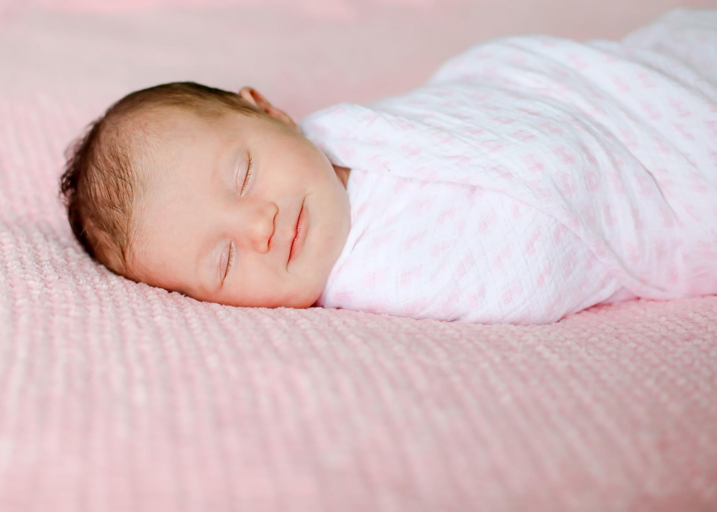 smiling newborn pink blanket.jpg