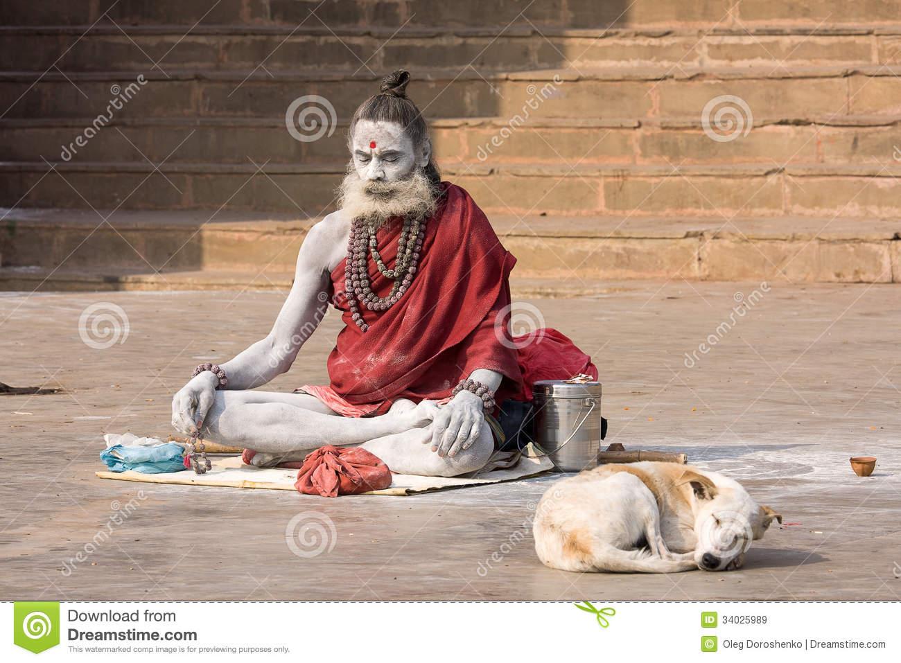 varanasi-india-december-unidentified-sadhu-sits-ghat-along-ganges-december-tourism-has-drawn-34025989.jpg